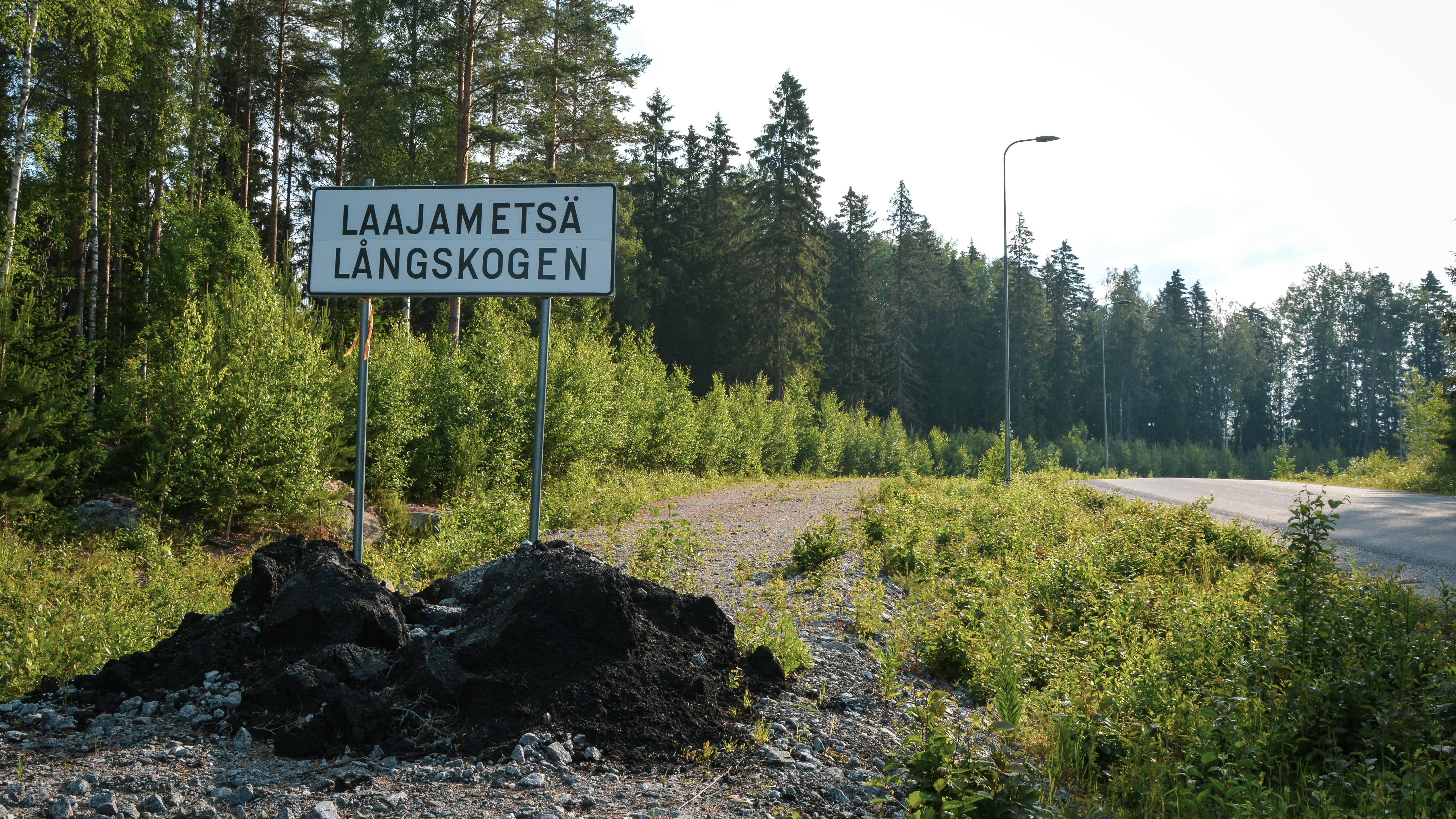 Asfaltoitu tie ja kyltti metsän reunassa jossa lukee Laajametsä.
