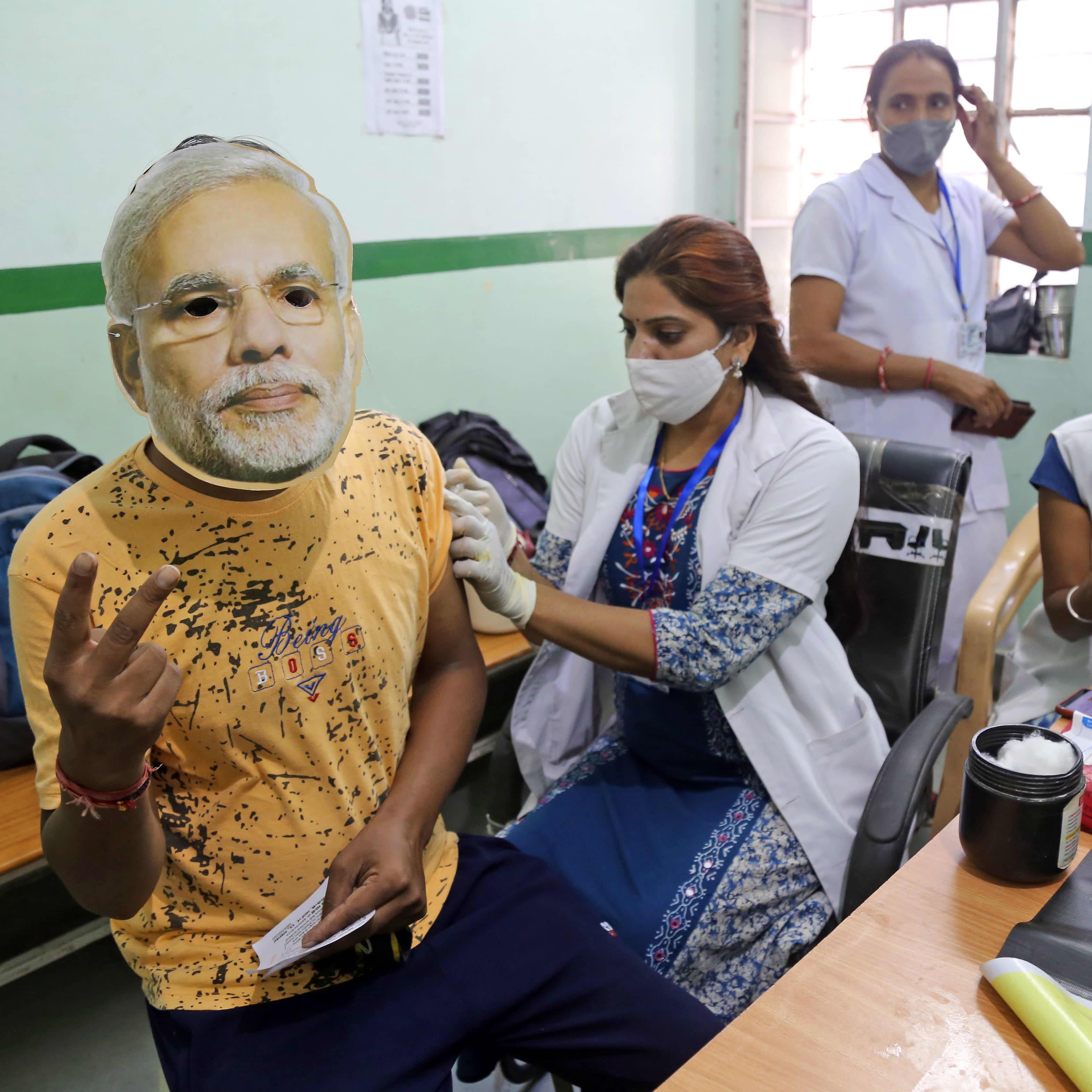 Terveydenhoitaja antaa koronarokottetta intialaiselle henkilölle.
