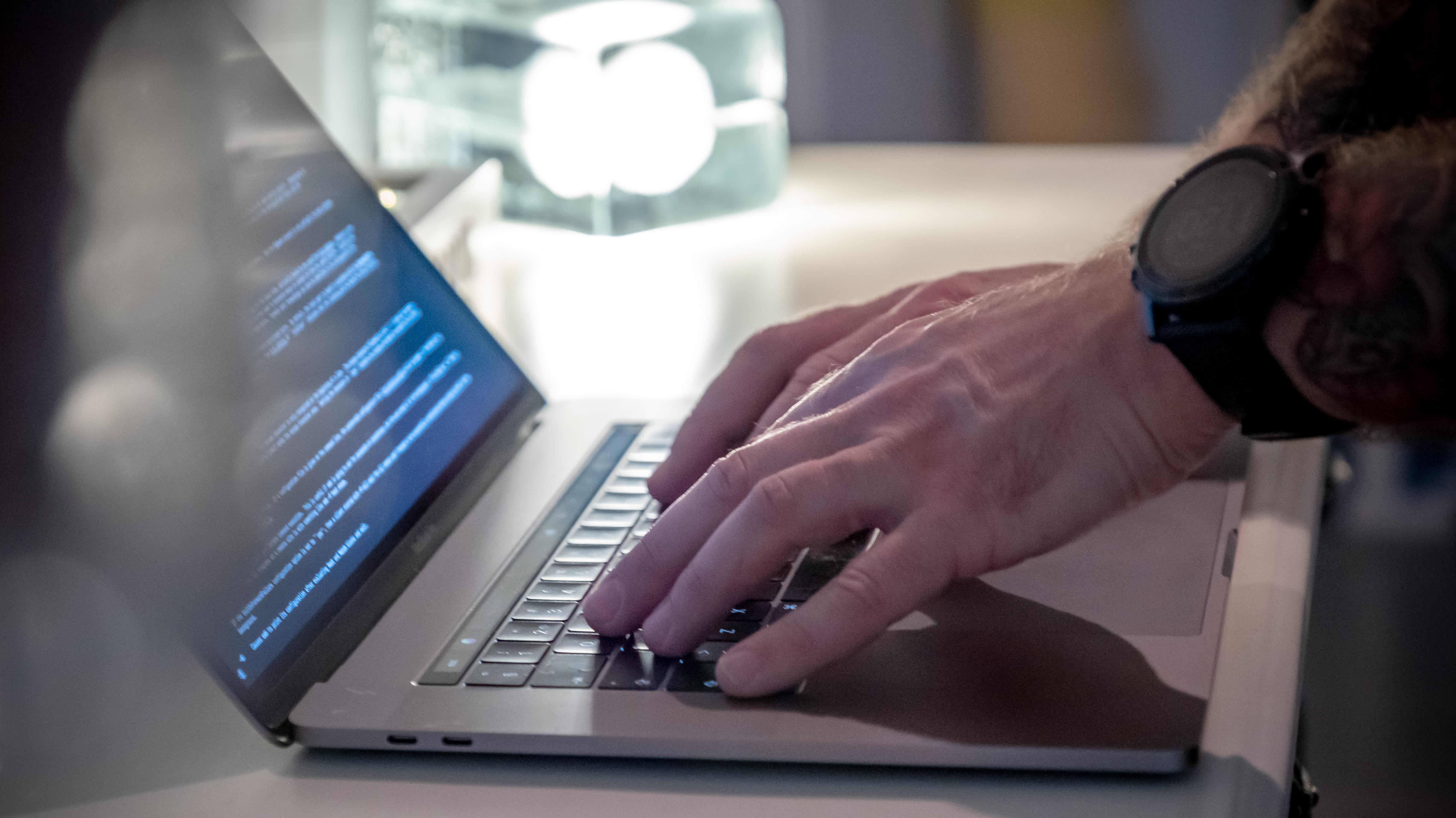 Lähikuva: mies kirjoittaa kannettavalla tietokoneella.