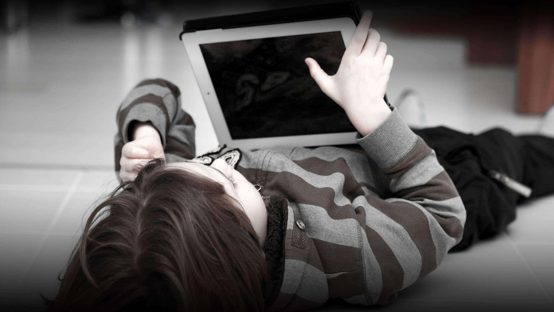 Flicka ligger på rygg på golvet med pekplatta i handen. Bleka färger.