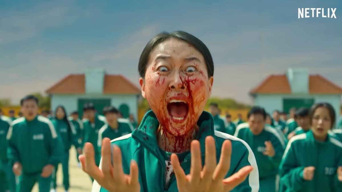 Nainen katsoo verisiä käsiään. Kasvoilleen on myös roiskunut verta.