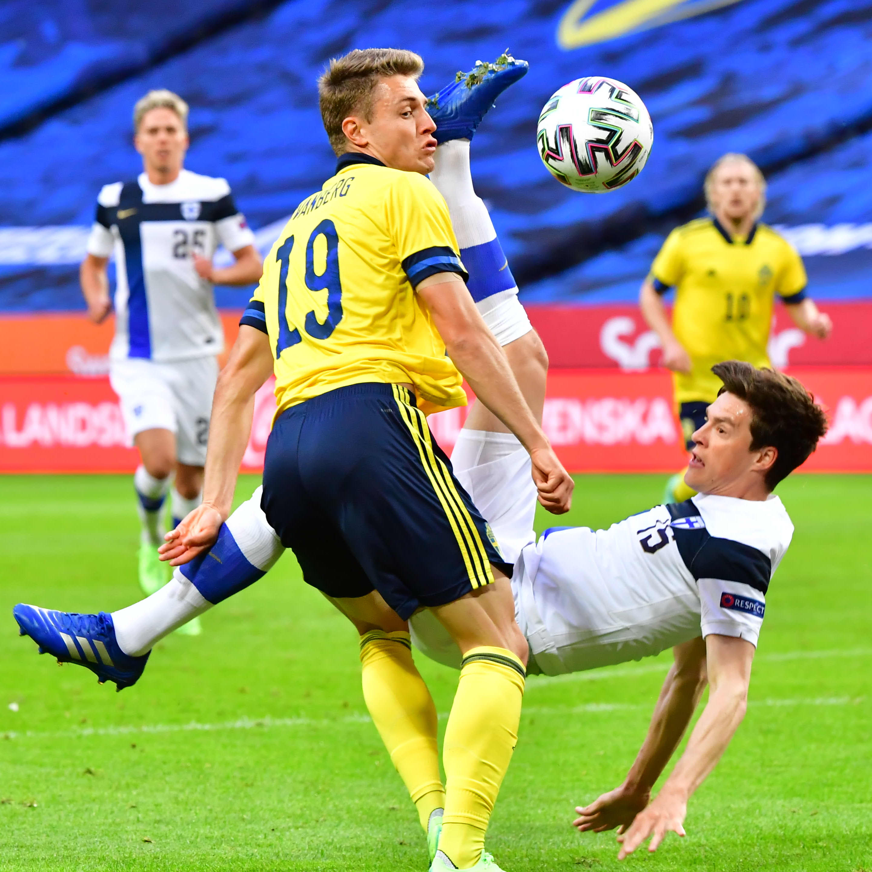 Finländsk fotbollsspelare i vitt ligger i luften och sparkar bort bollen framför svensk spelare i gult.