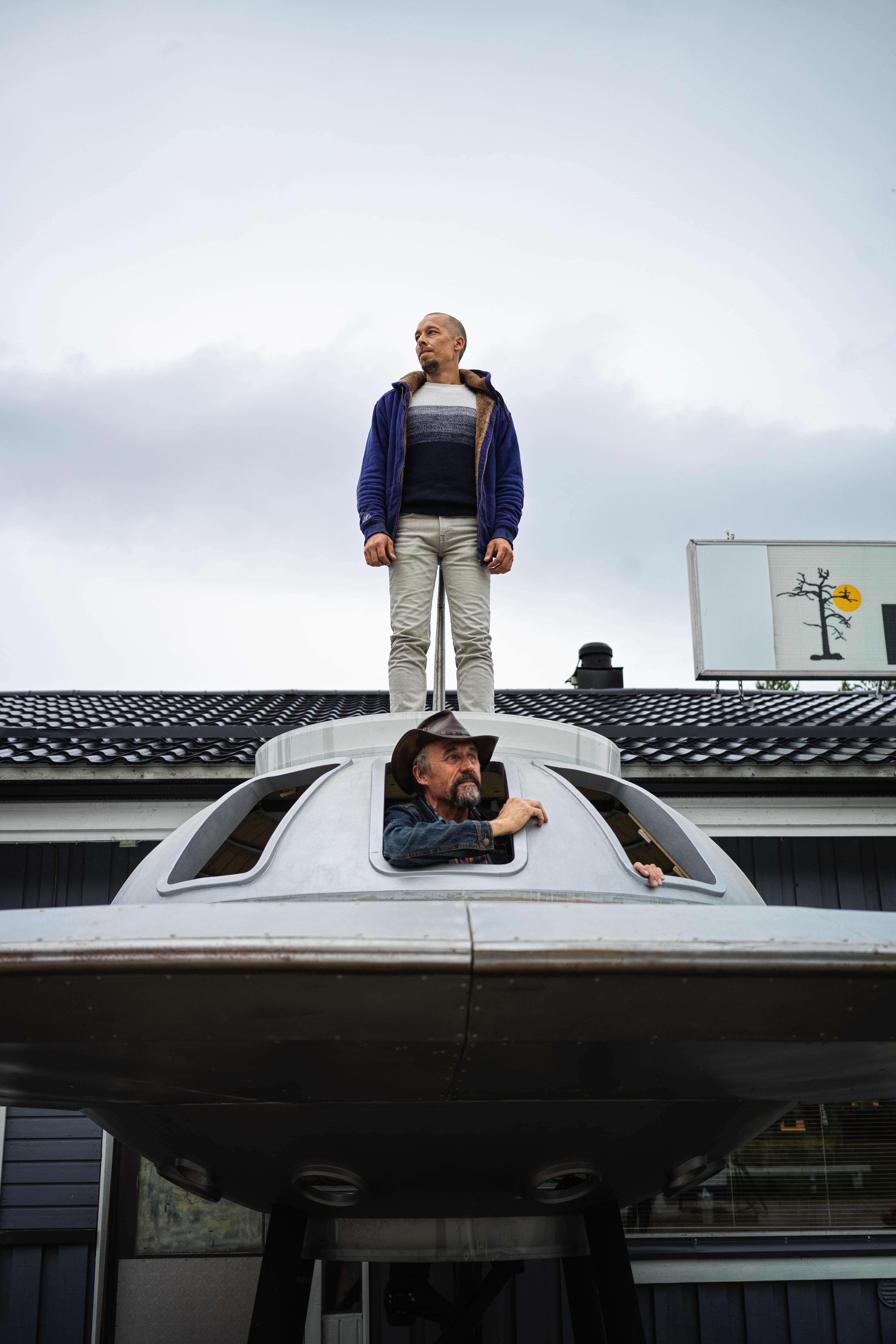 Kaksi henkilöä lentävälautasen kyydissä