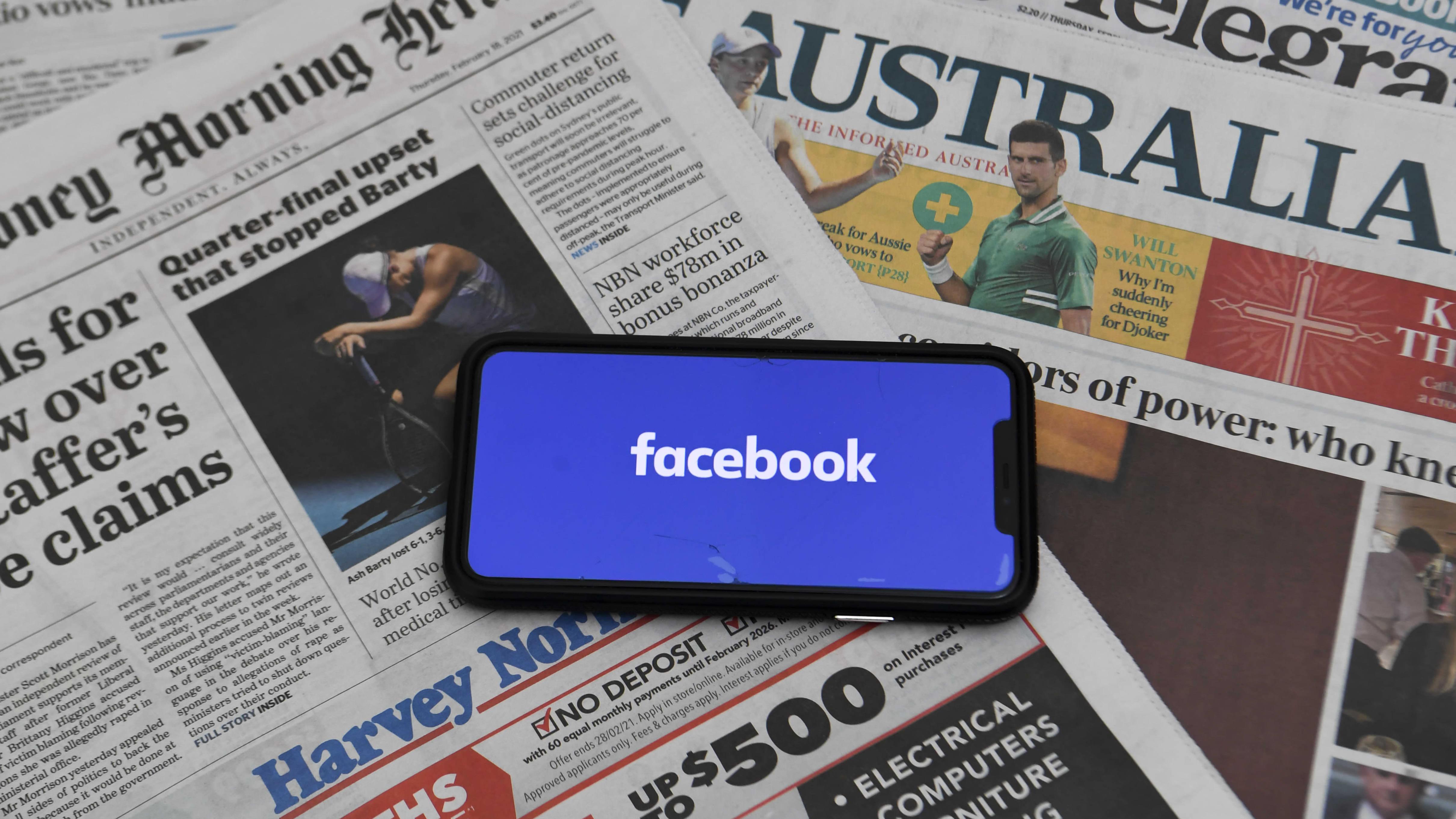 En mobiltelefon med texten facebook på skärmen. Mobiltelefonen ligger på en hög med tidningar från Australien.