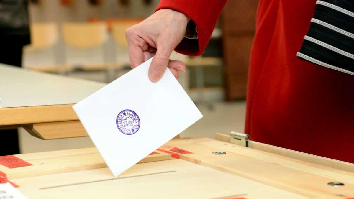 En person lägger in en valsedel med stämpel på i en box av trä.