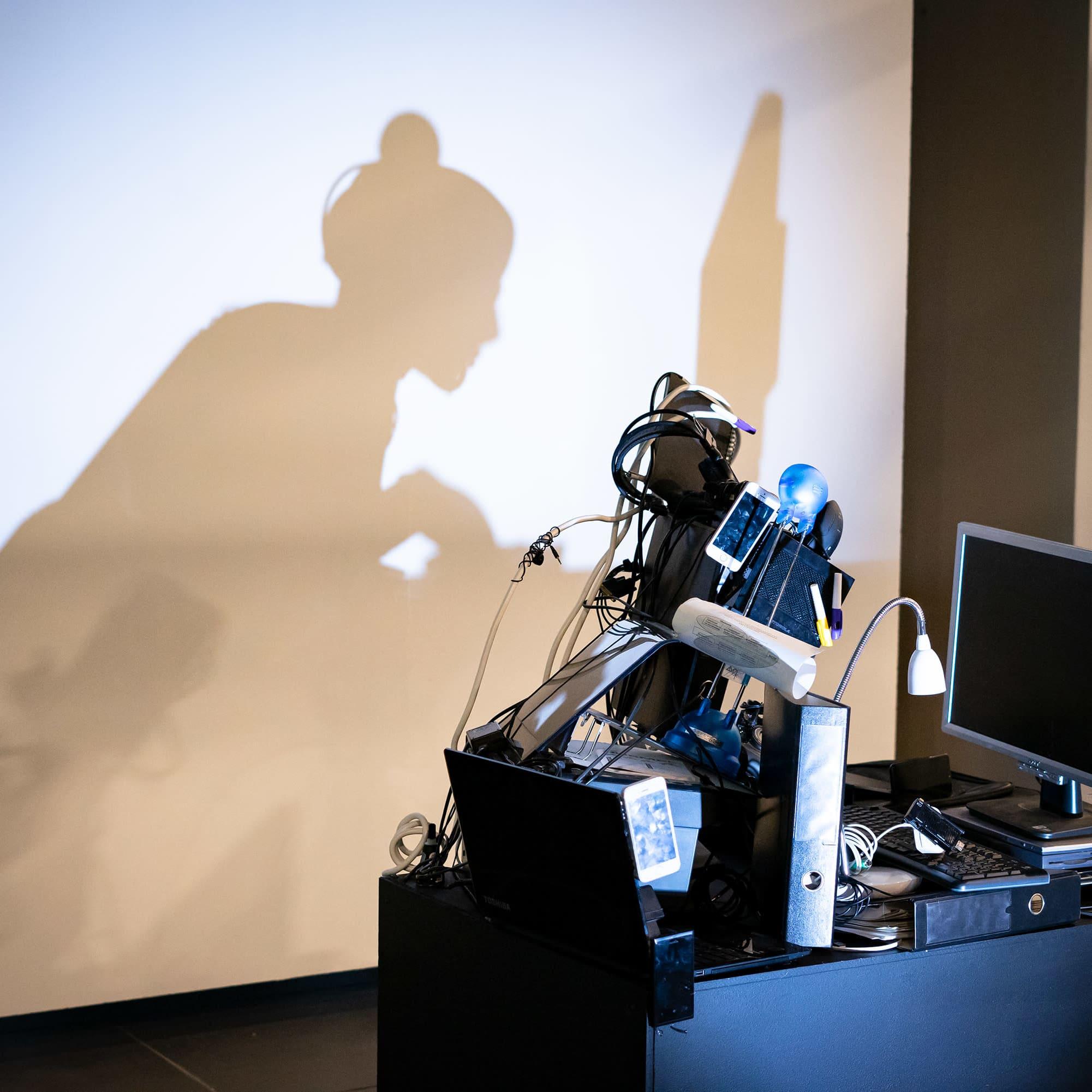Kuvassa seinään heijastuu tietokoneen ääressä työskentelevä nainen.