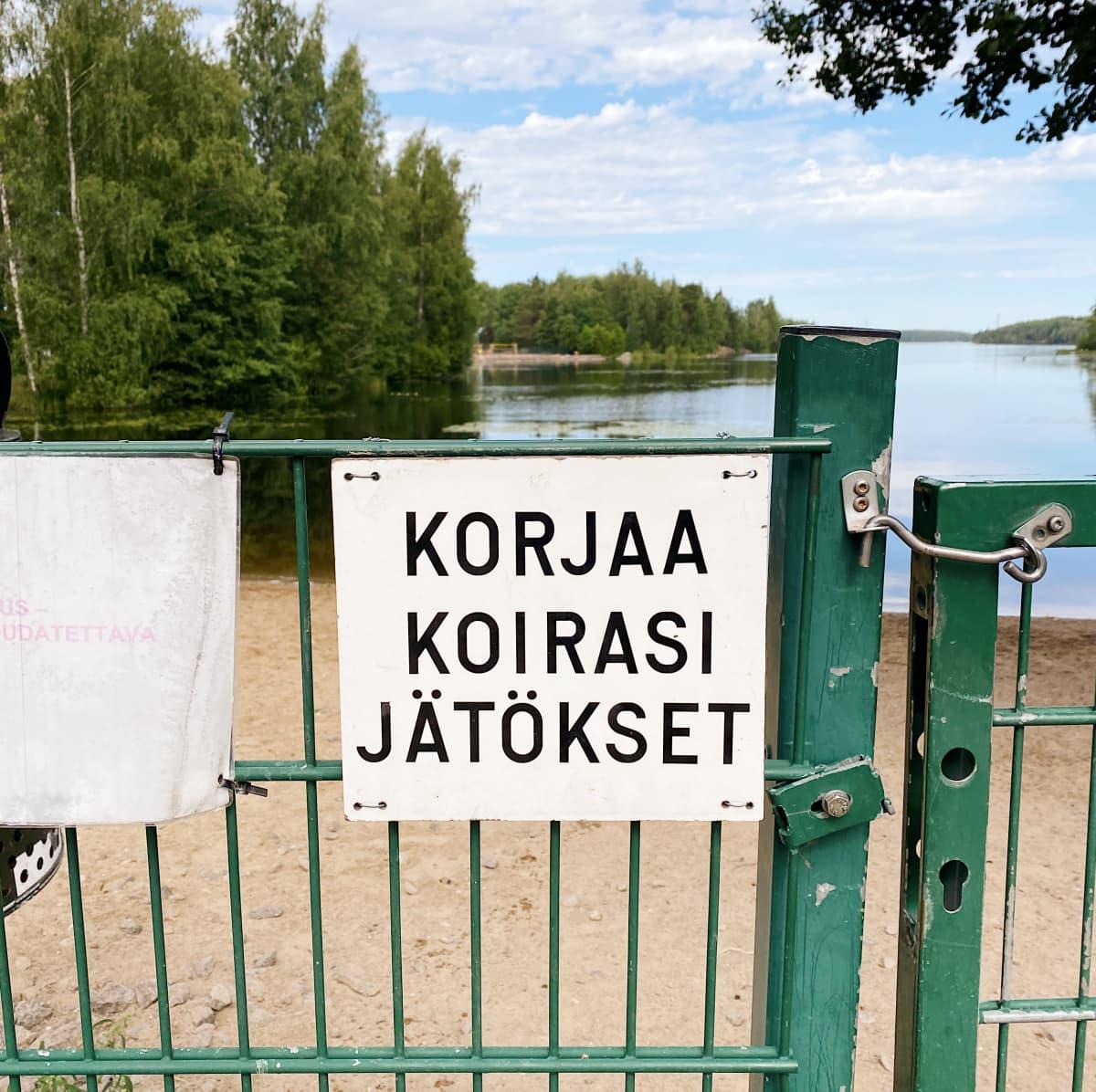 Korjaa koirasi jätökset -kyltti koirauimarannan aidassa. Taustalla Saimaa.