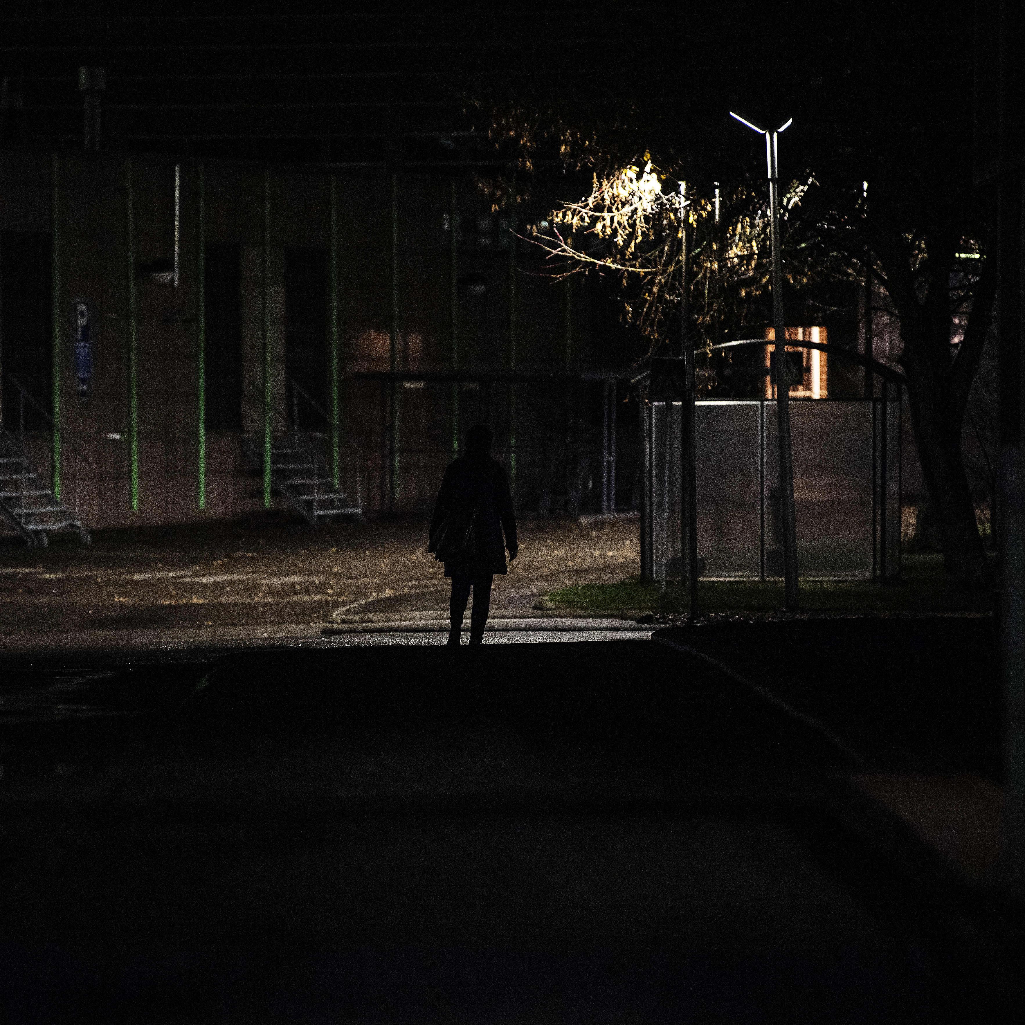 Tumma hahmo kävelee ulkona marraskuussa 2020.