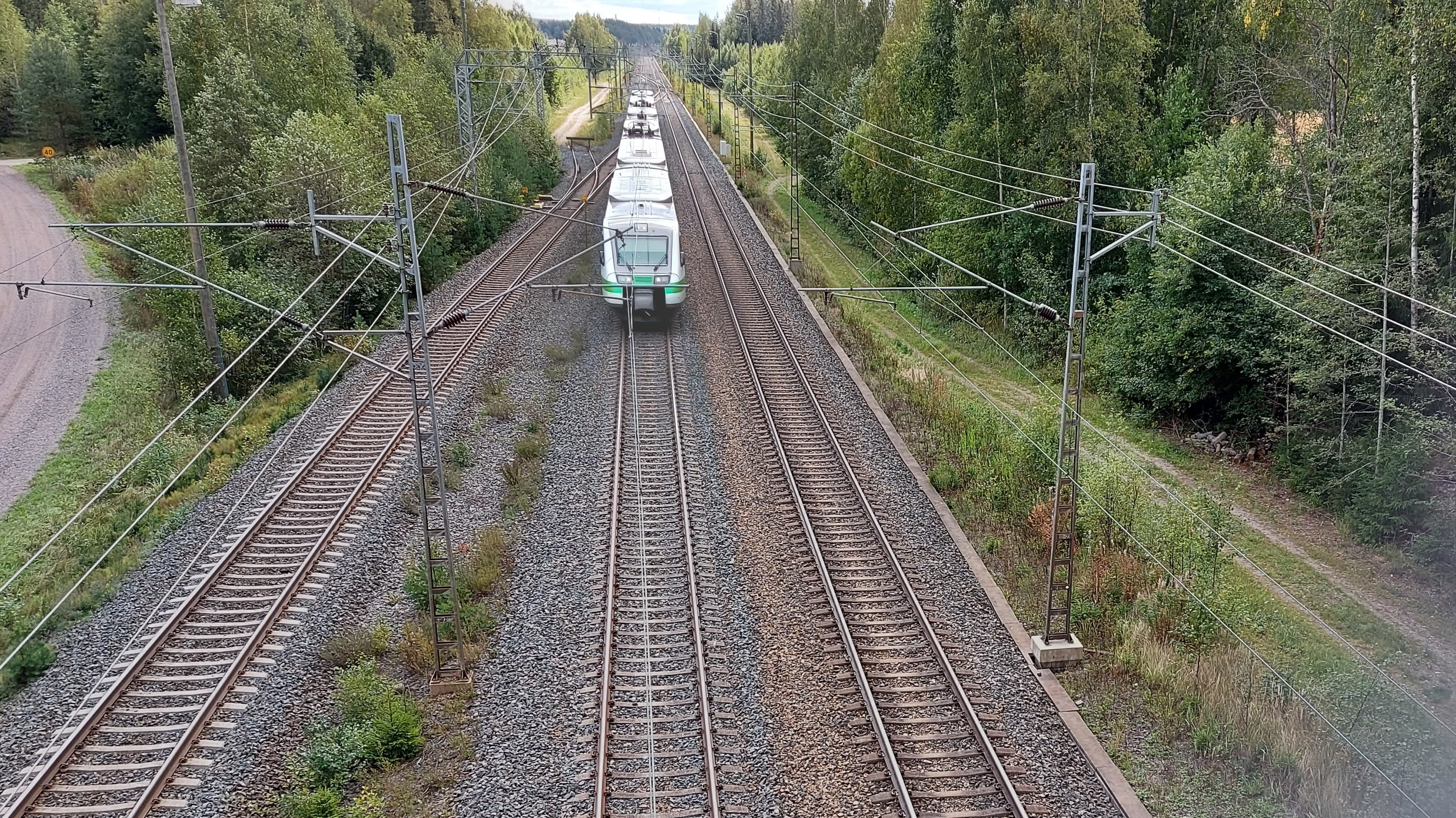 Ylhäältä ylikulkusillalta kuvattu junarata, jossa lähijuna tulee kohti kameraa.