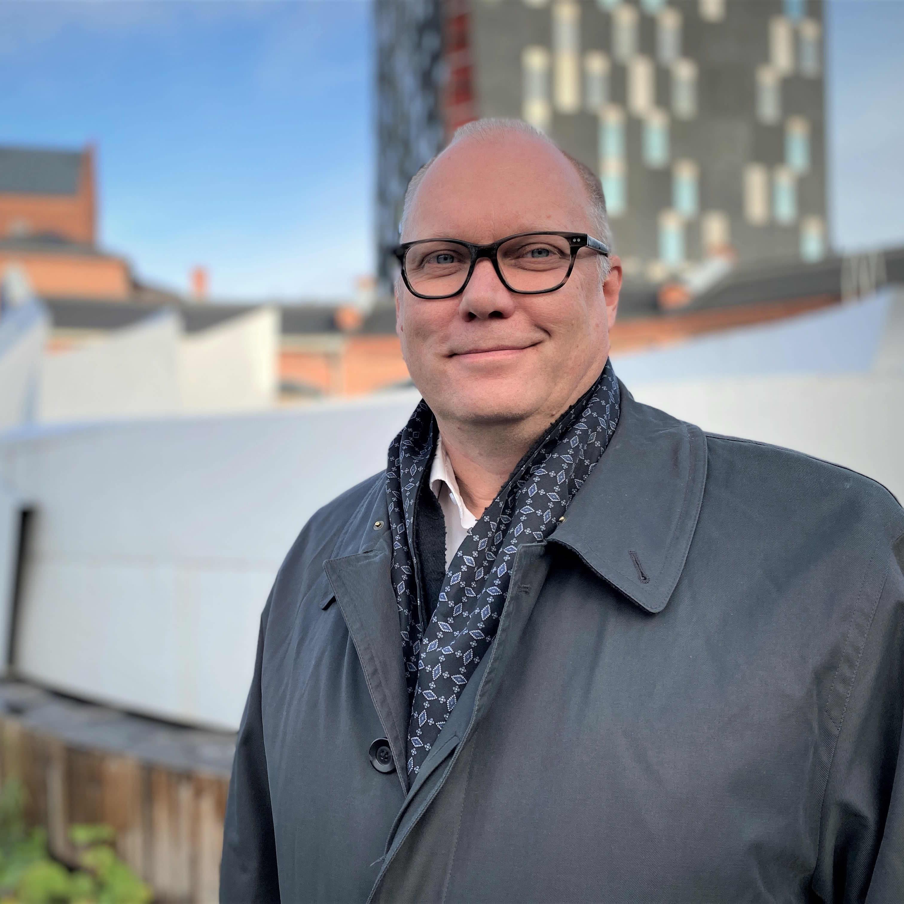 Hymyilevä mies seisoo Tampereella korkea tornitalo taustalla.