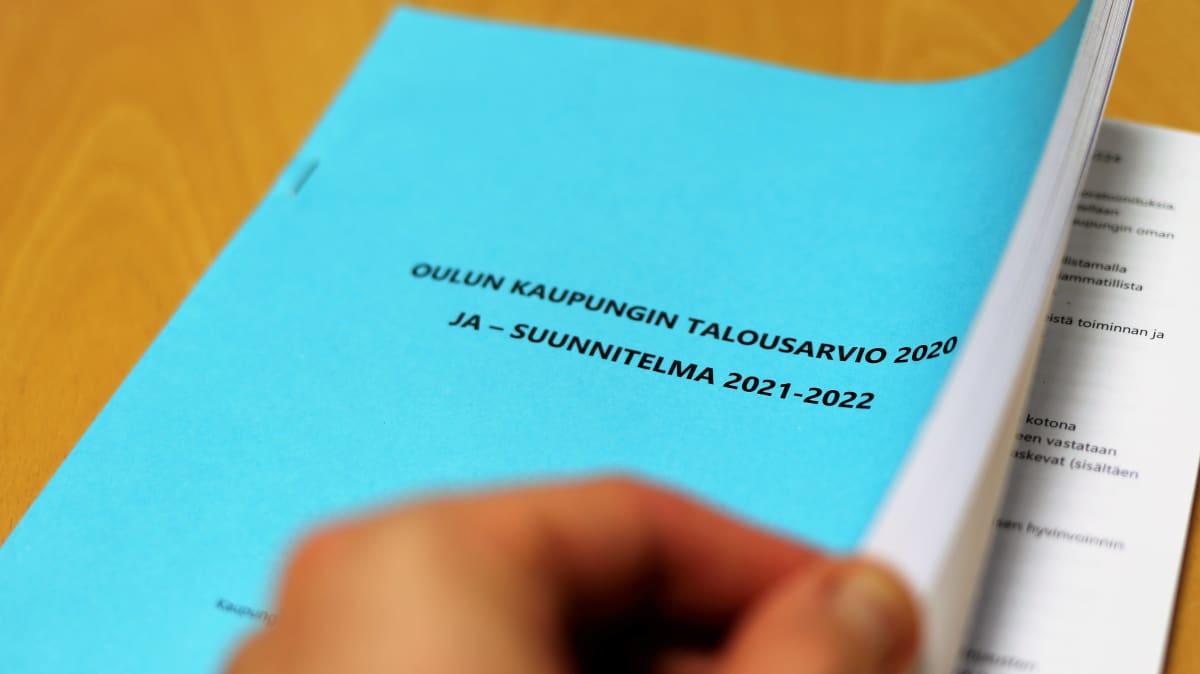 Käsi selailee Oulun talousarvio -vihkoa.