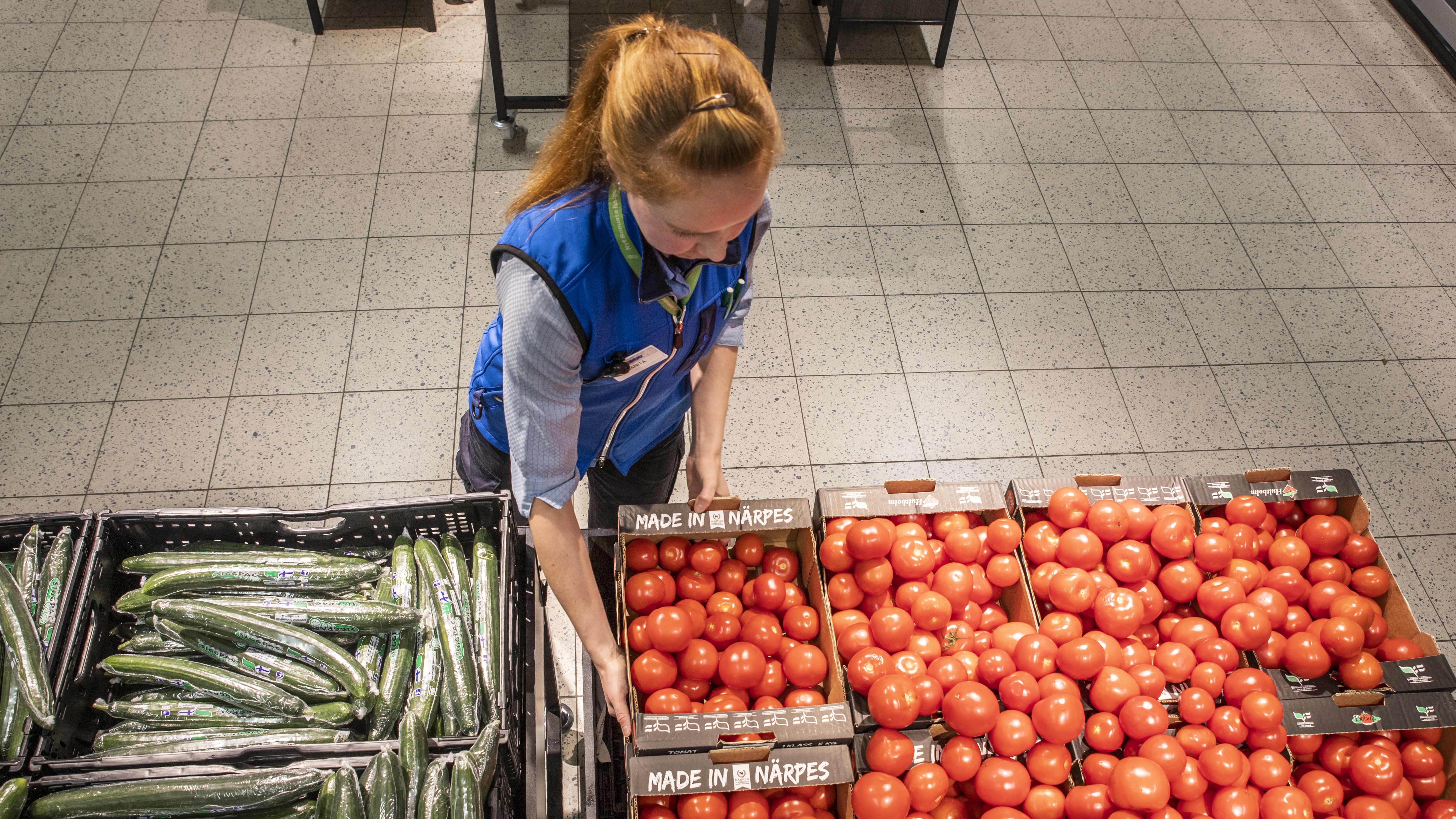 Janita Rahikainen täyttämässä vihanneshyllyjä S-Marketissa.