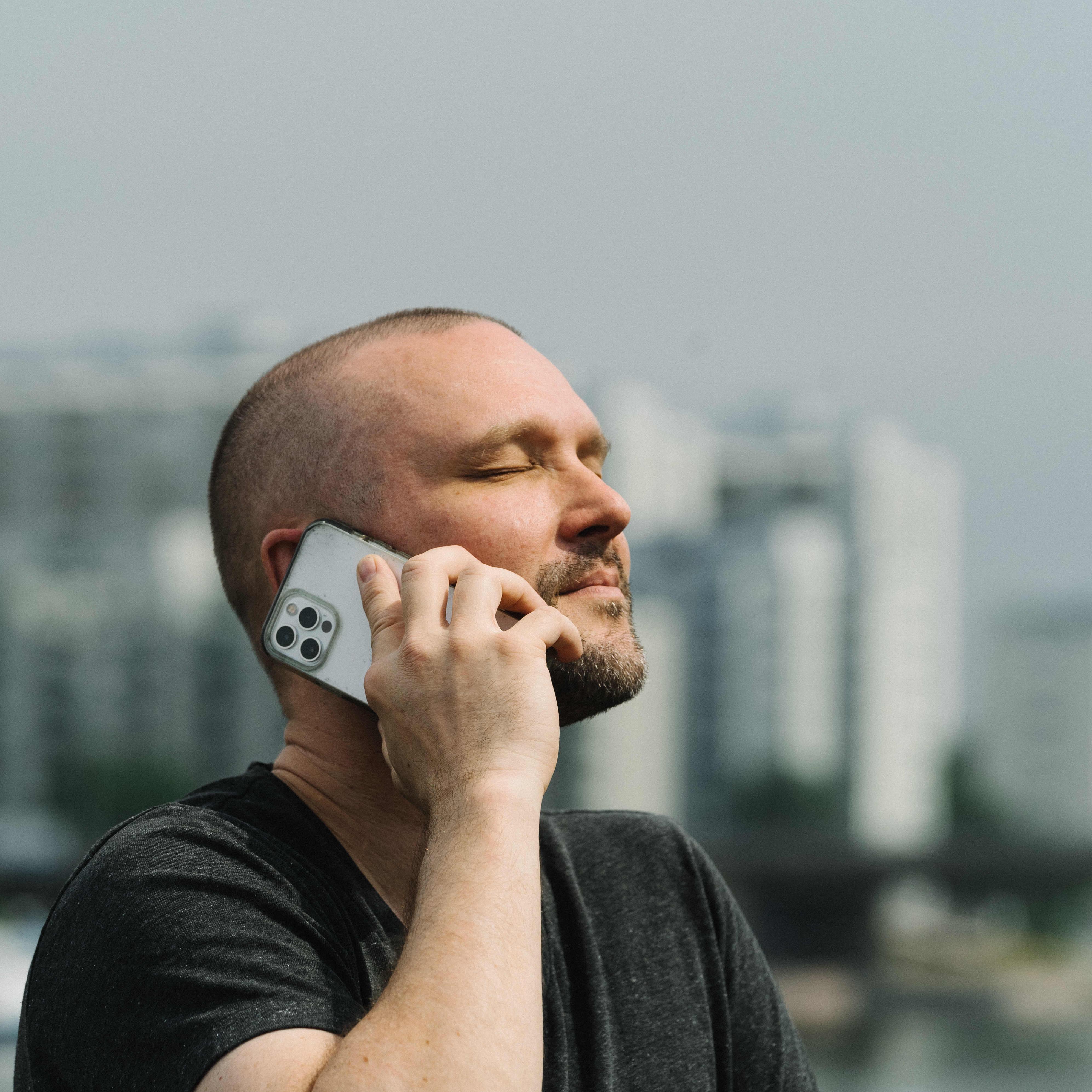 Tommi Koivisto puhuu kännykkään. Taustalla kaupinkimaisema.