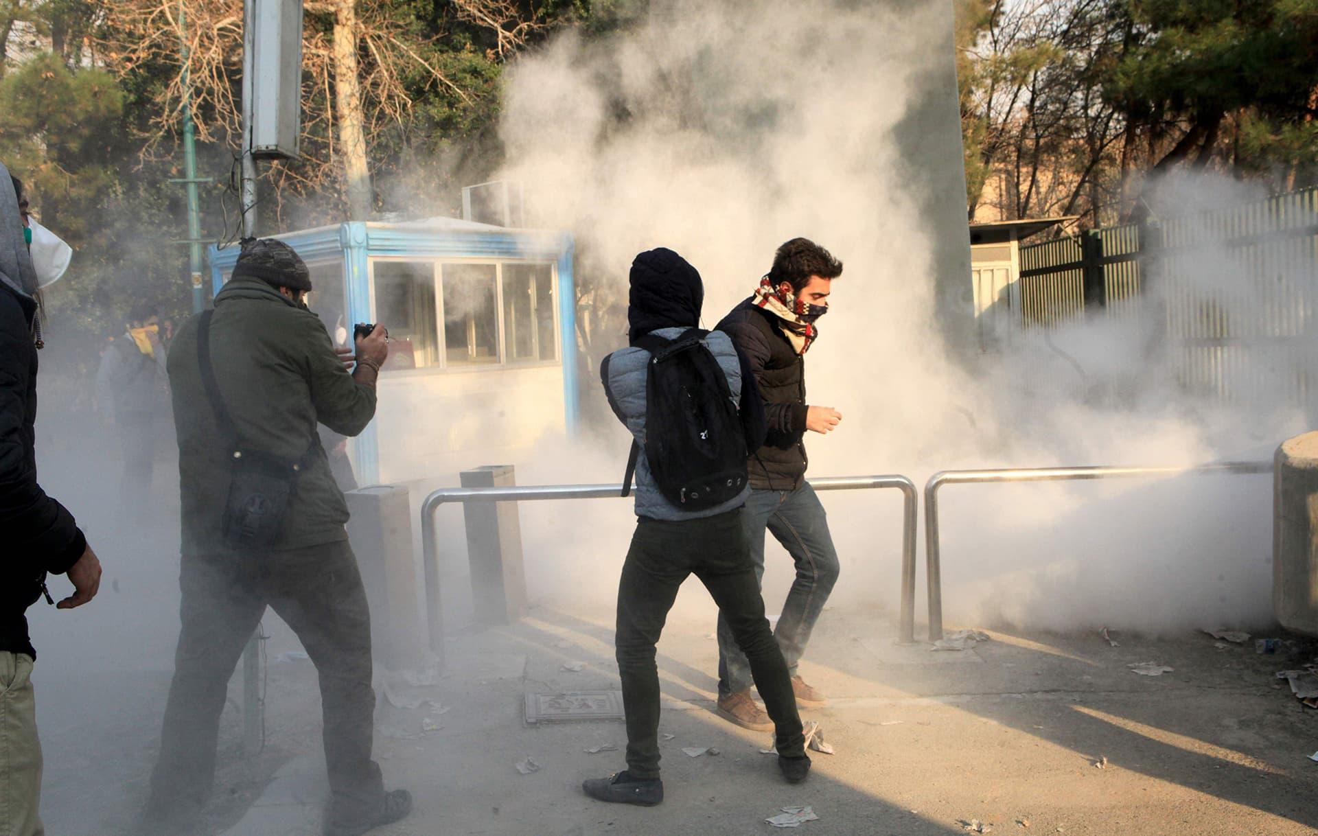 Iranilaisopiskelijat yrittivät suojautua kyynelkaasulta mielenosoituksessa Teheranin yliopistolla lauantaina.