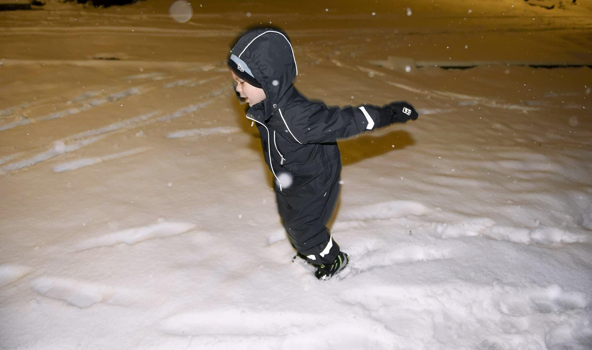 Poika leikkii lumella.