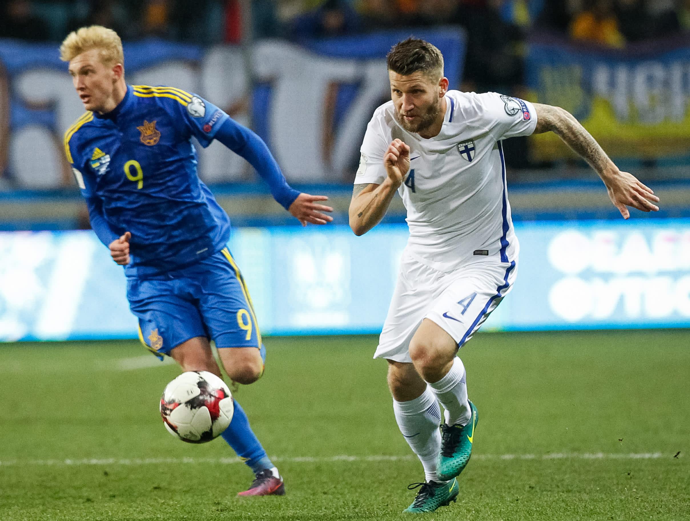 Huuhkajien Joona Toivio ja Ukrainan Viktor Kovalenko juoksevat pallon perässä.