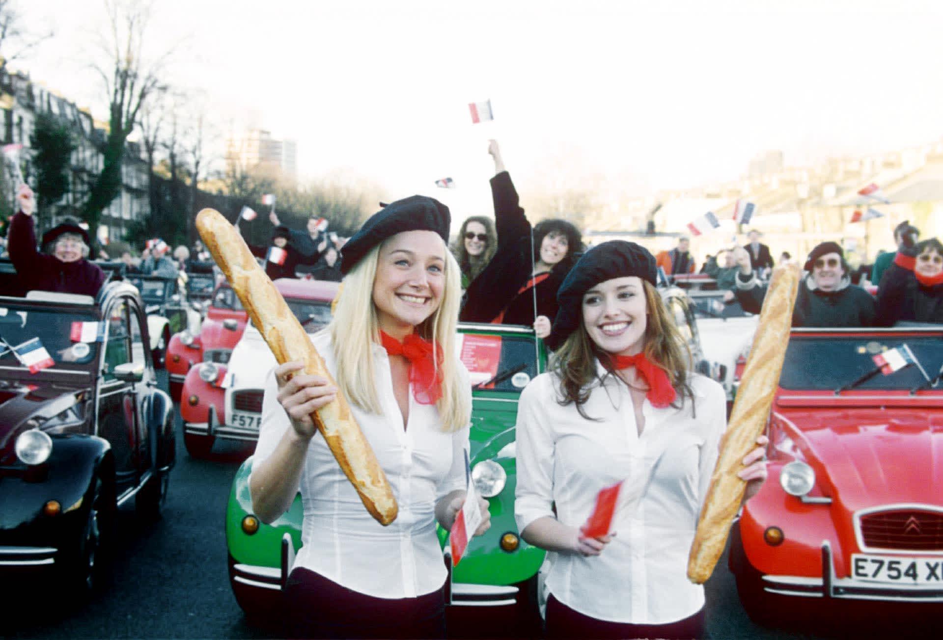 Baskeriin pukeutuneet naiset heiluttelevat patonkeja Citroen-autojen kokoontumisajoissa.