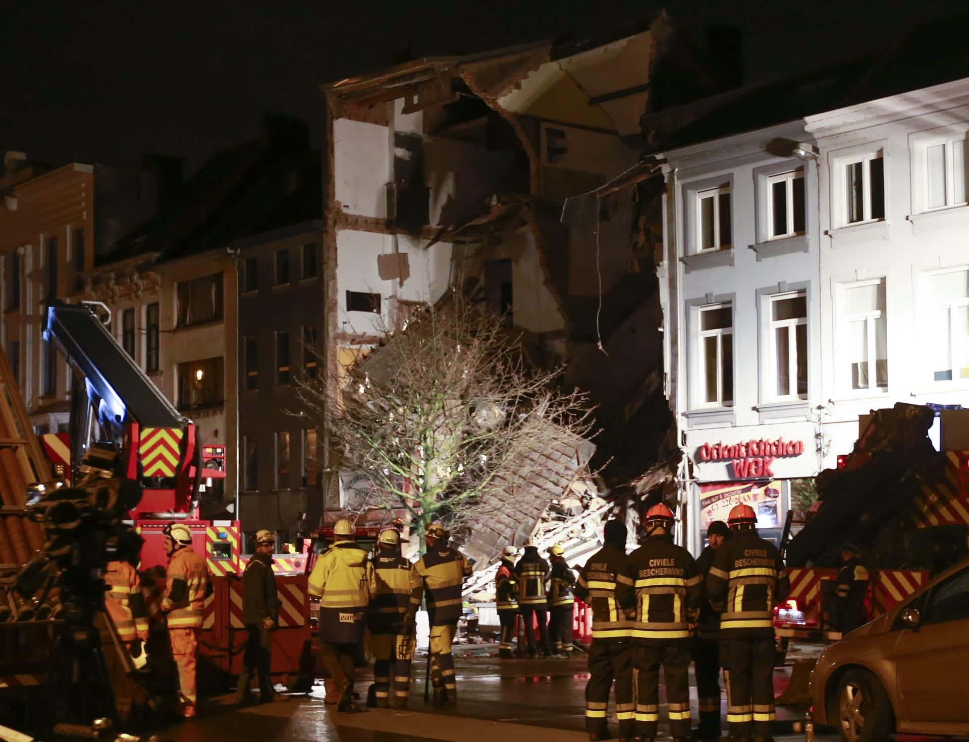Kuvassa pelastustyöntekijät seisovat onnettomuuspaikalla ja katsovat näkyä, jossa kerrostalon koko julkisivu on irronnut ja tuhoutunut.