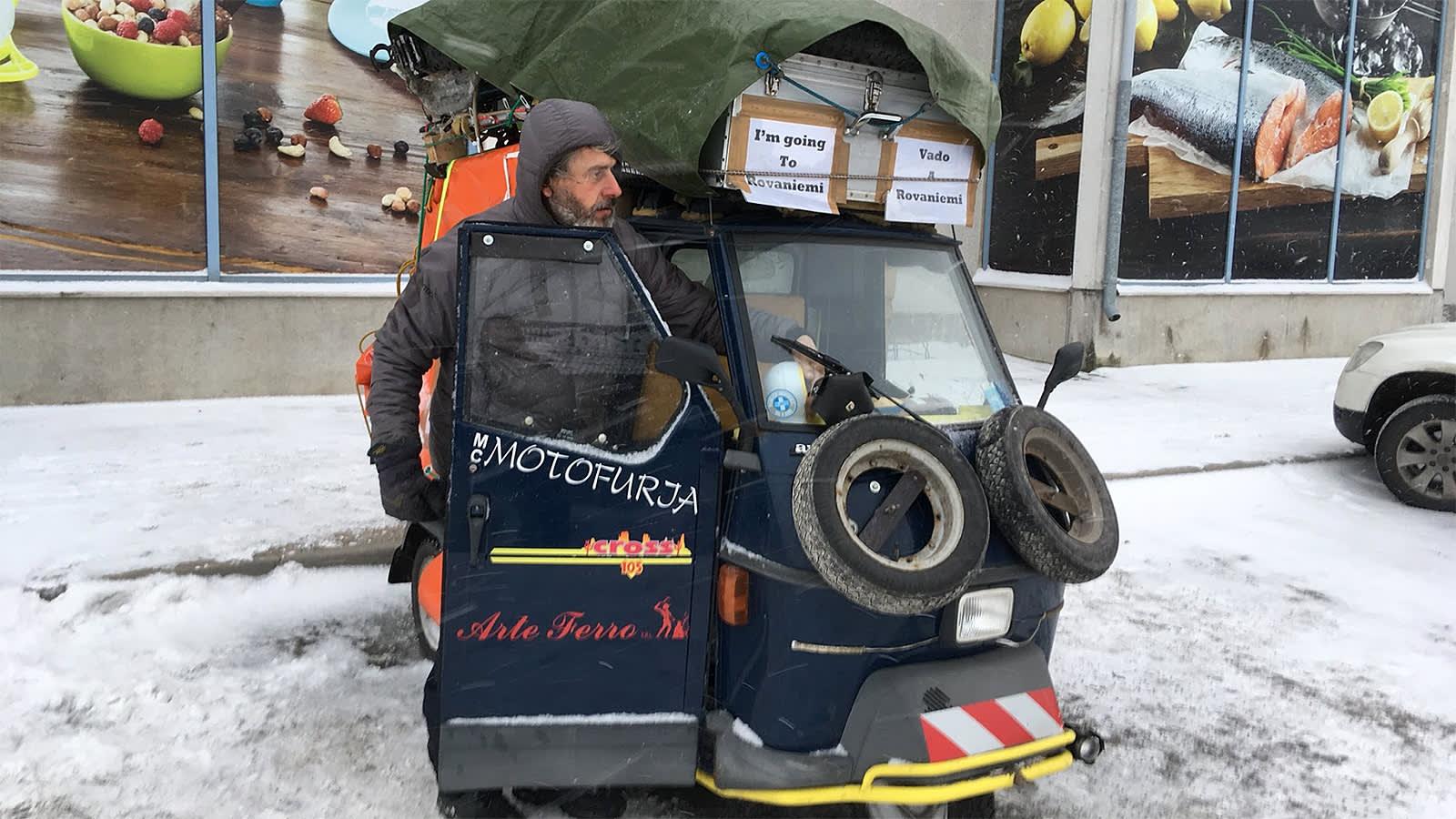Mies ja hänen täyteen lastattu tavaramoponsa kaupan parkkipaikalla