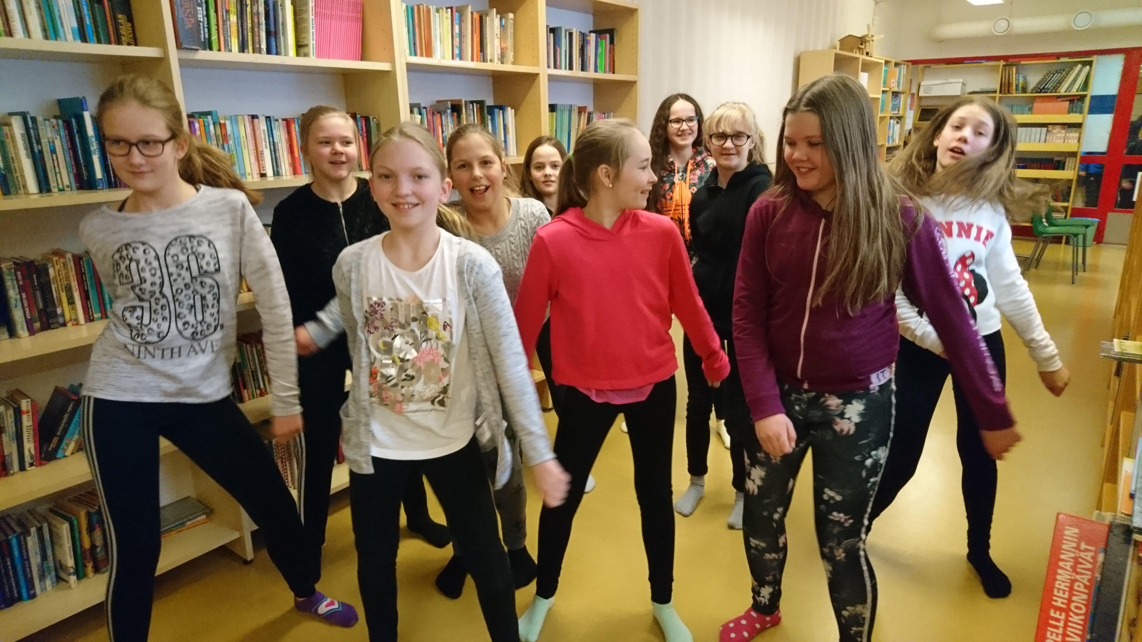 Tytöt tanssivat koulun kirjastossa.