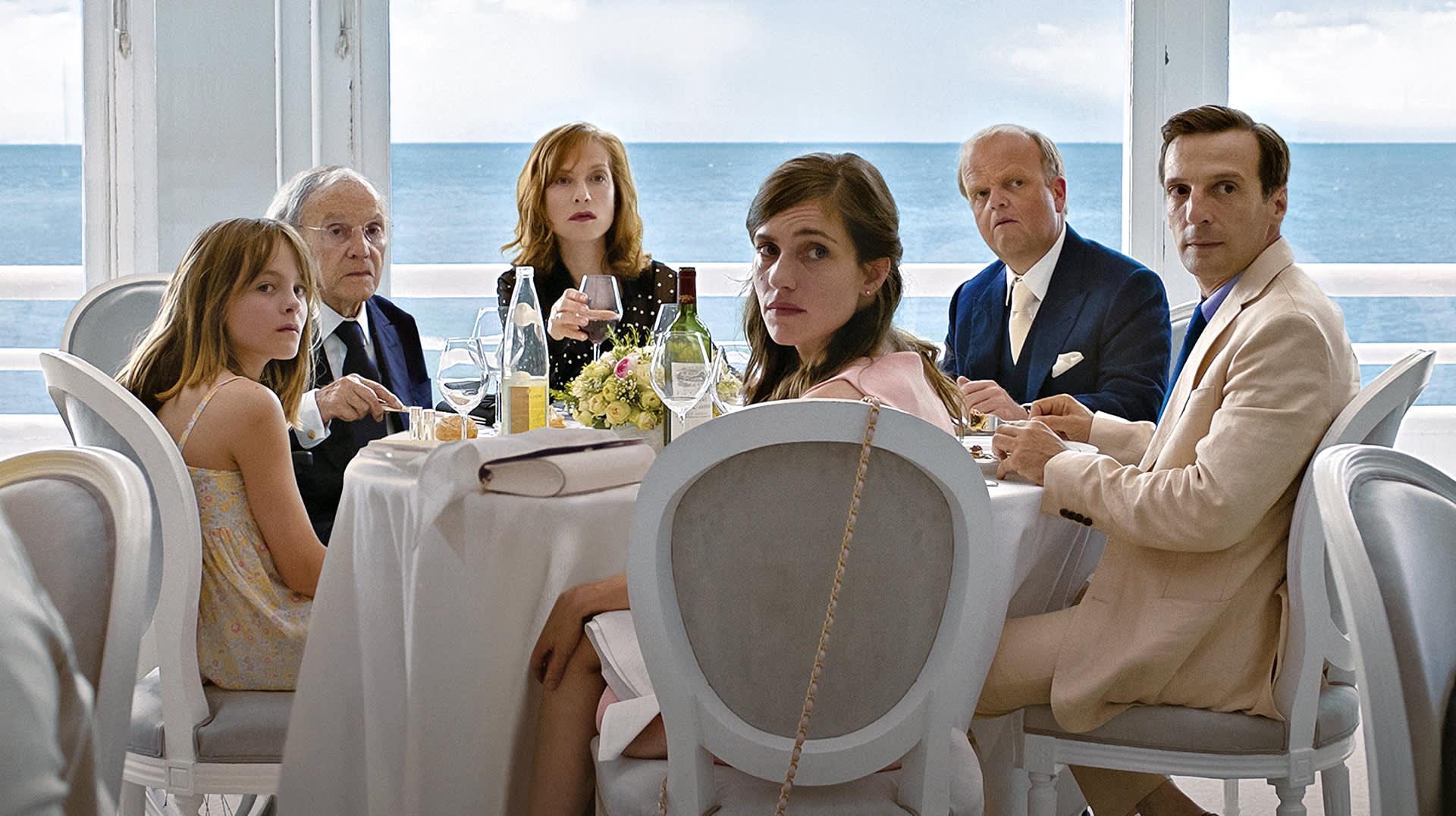 Laurentin perhe on pöydän ääressä kääntyneenä katsomaan kohti kameraa.