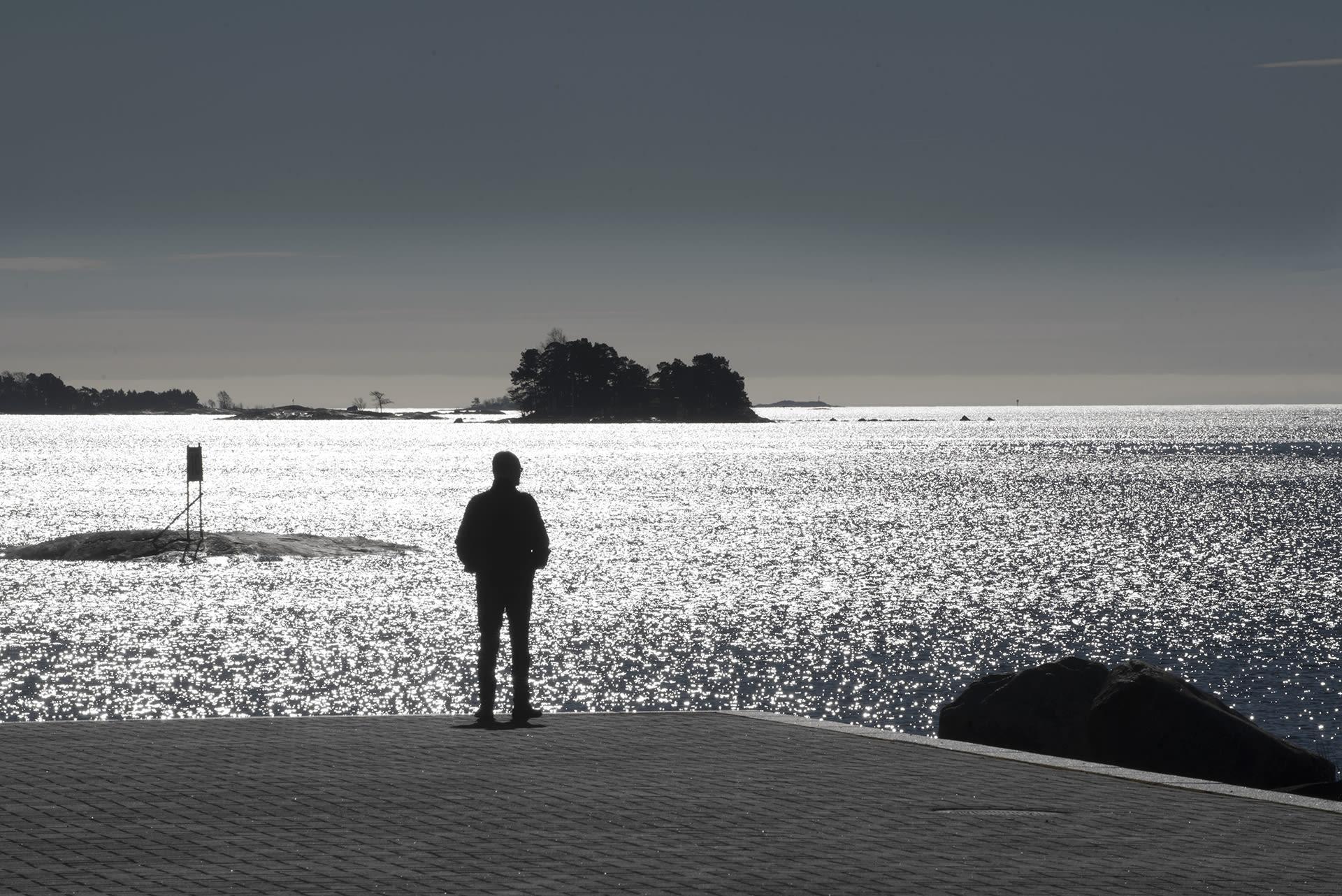 Mies seisoo laiturilla ja katsoo merelle