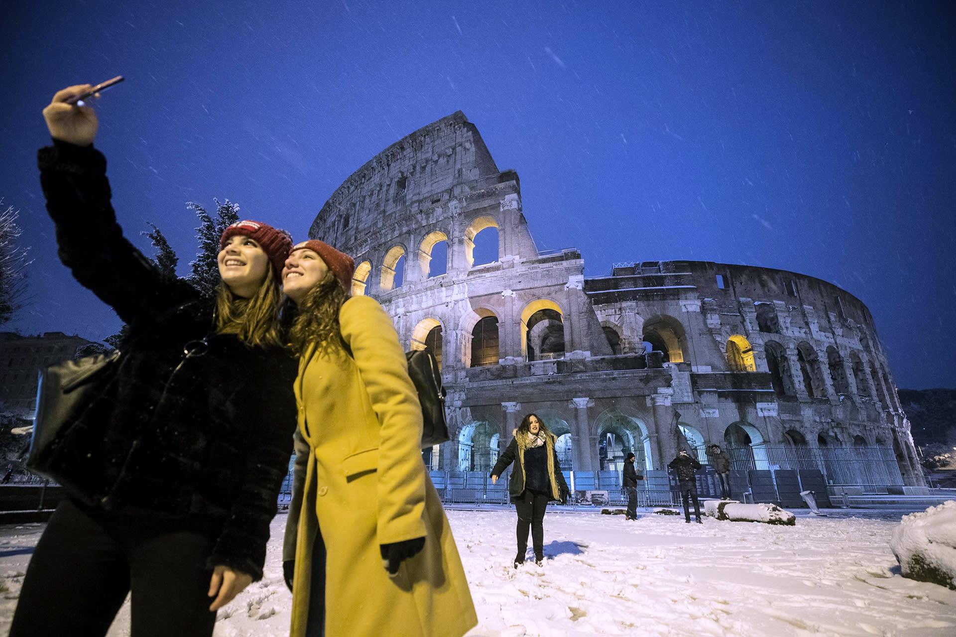 Turistit valokuvaavat lumisen Colosseumin edustalla  Roomassa.
