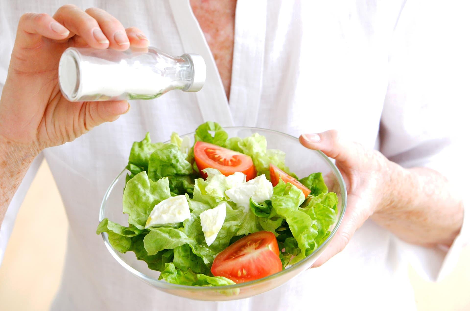 nainen laittaa suolaa salaattiin