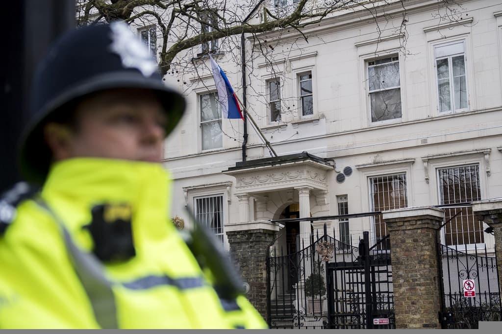 Brittiläinen poliisimies seisoo keltaisissa huomioliiveissä, perinteinen bobby-hattu päässään vartiossa Venäjän vaalean suurlähetystörakennuksen edessä. Puissa ei ole lehtiä. Suurlähetystön julkisivulla on Venäjän lippu.