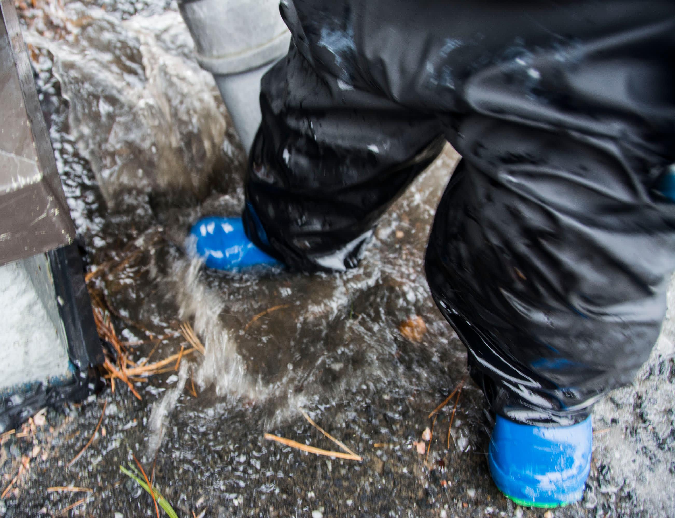 Lapsi hyppii kuralätäkössä ja läiskyttelee vettä.