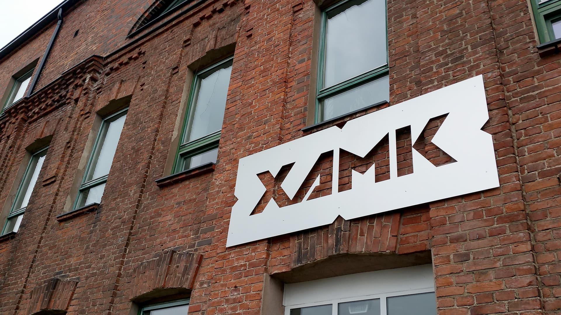 Xamkin tunnus Kouvolan kampuksen tiiliseinässä.