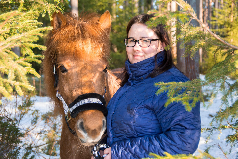 Tiia-Maria Joensuu seisoo metsikössä Mansikka-hevosen vieressä.