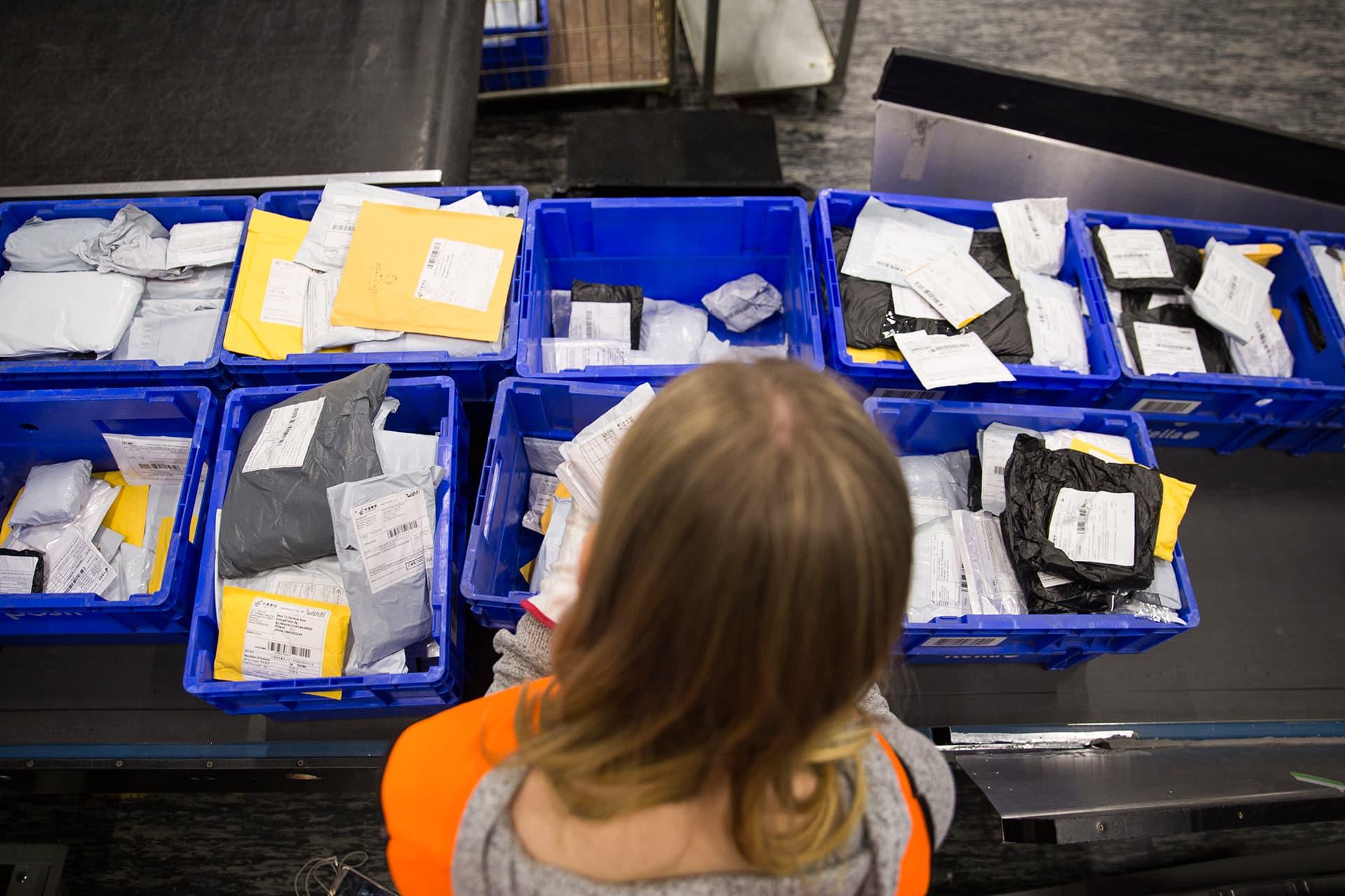 Nainen lajittelee postilähetyksiä.
