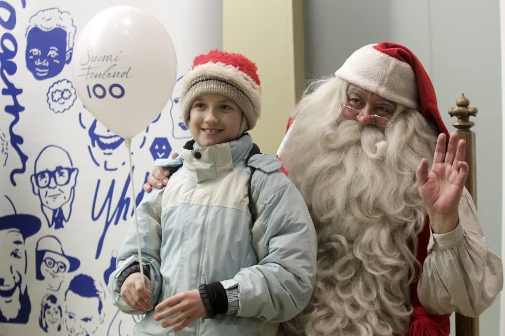 Suomi 100 -ilmapalloa pitelevä tonttulakkipäinen lapsi joulupukin kainalossa.