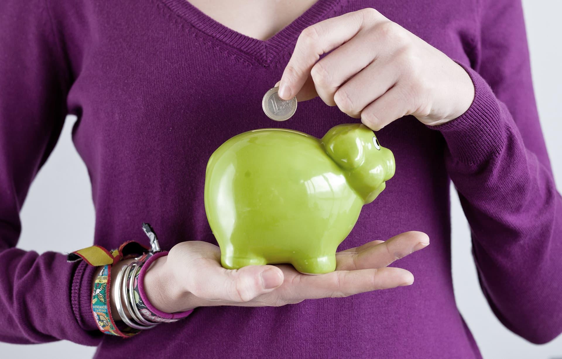 Nainen laittaa euron säästöporsaaseen.