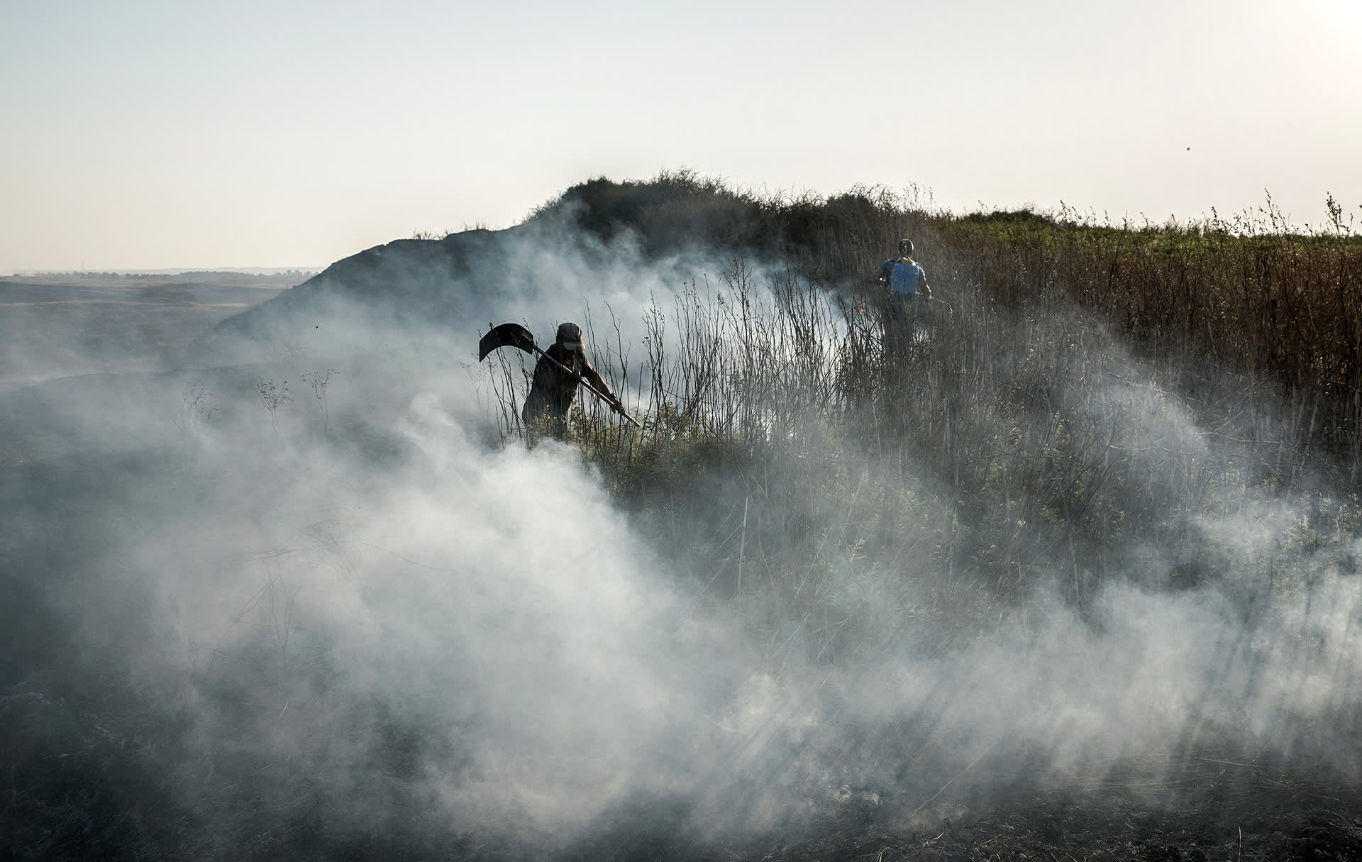 Miehet sammuttavat maastopaloa Israelissa.