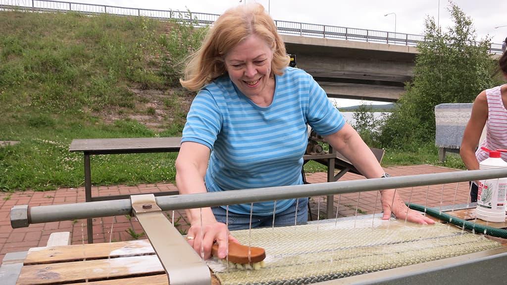 Aino Davidila Korkalovaarasta pesee mattoa Rovaniemen Lainaanrannassa