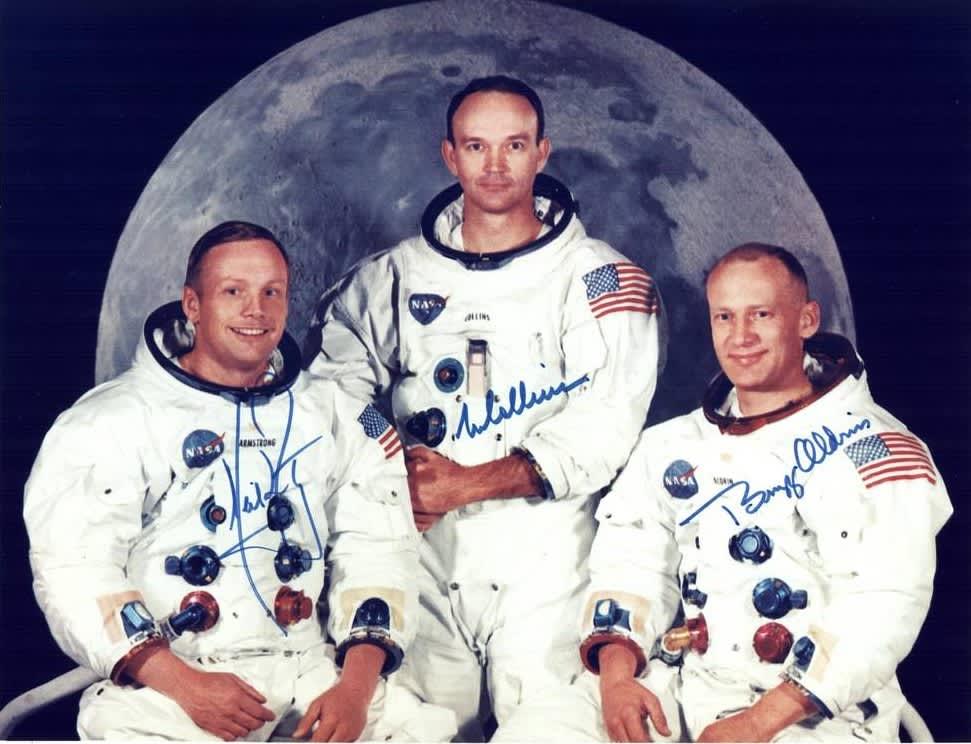 Kolme avaruuspukuista astronauttia Kuuta esittävän kuvan edessä.