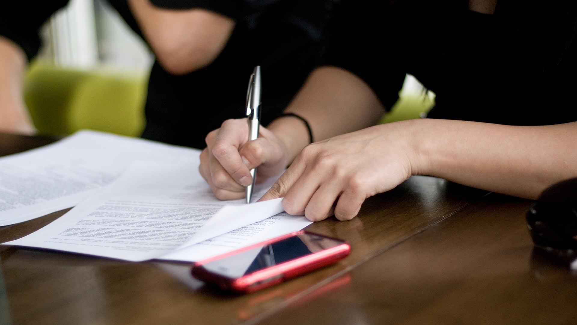 Henkilö kirjoittaa paperille.