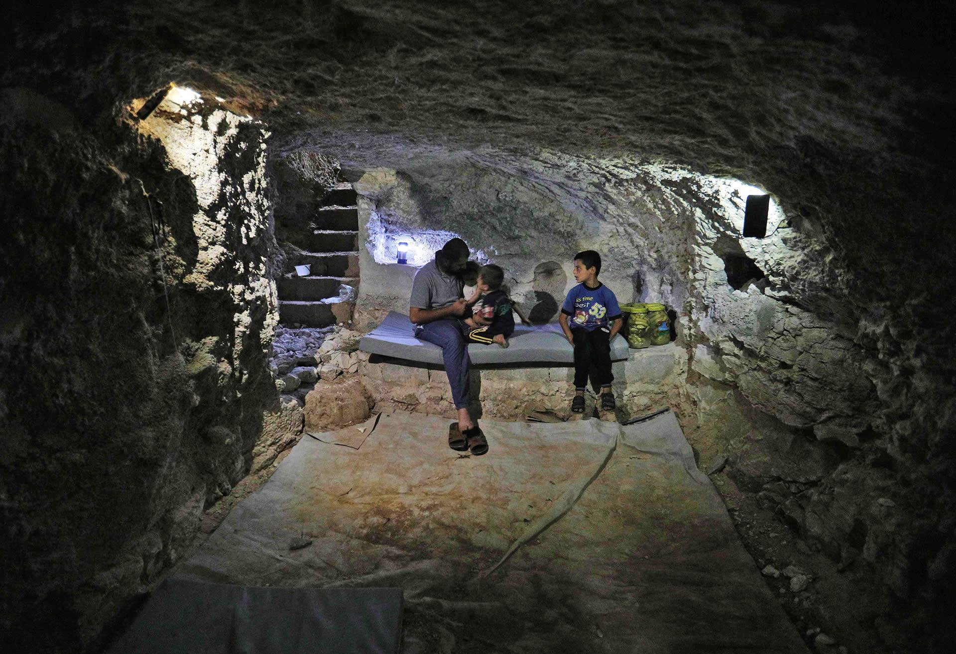 Mies ja kaksi laista istuvat luolassa.