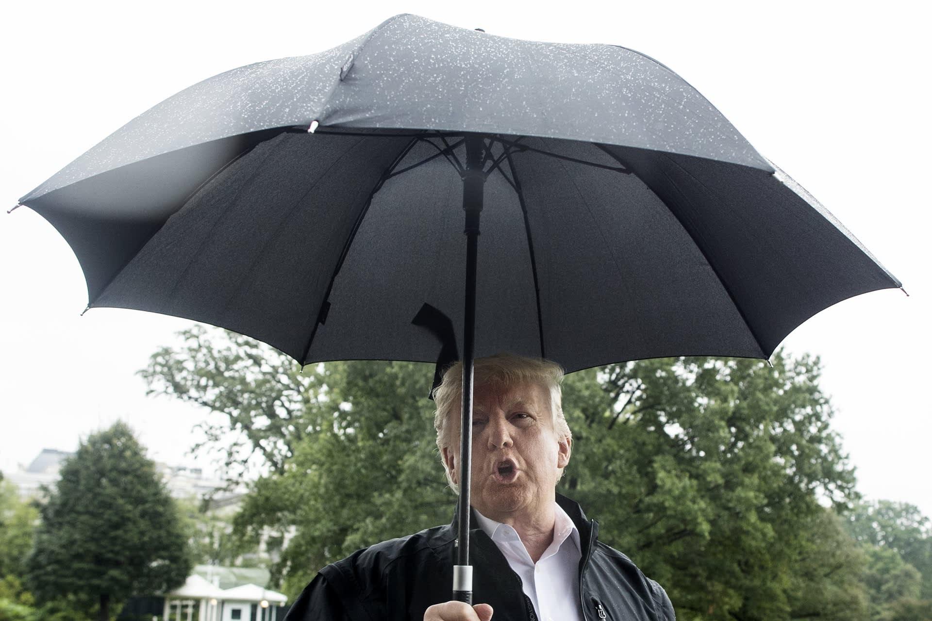 Yhdysvaltain presidentti Donald Trump puhuu sateenvarjon alta.