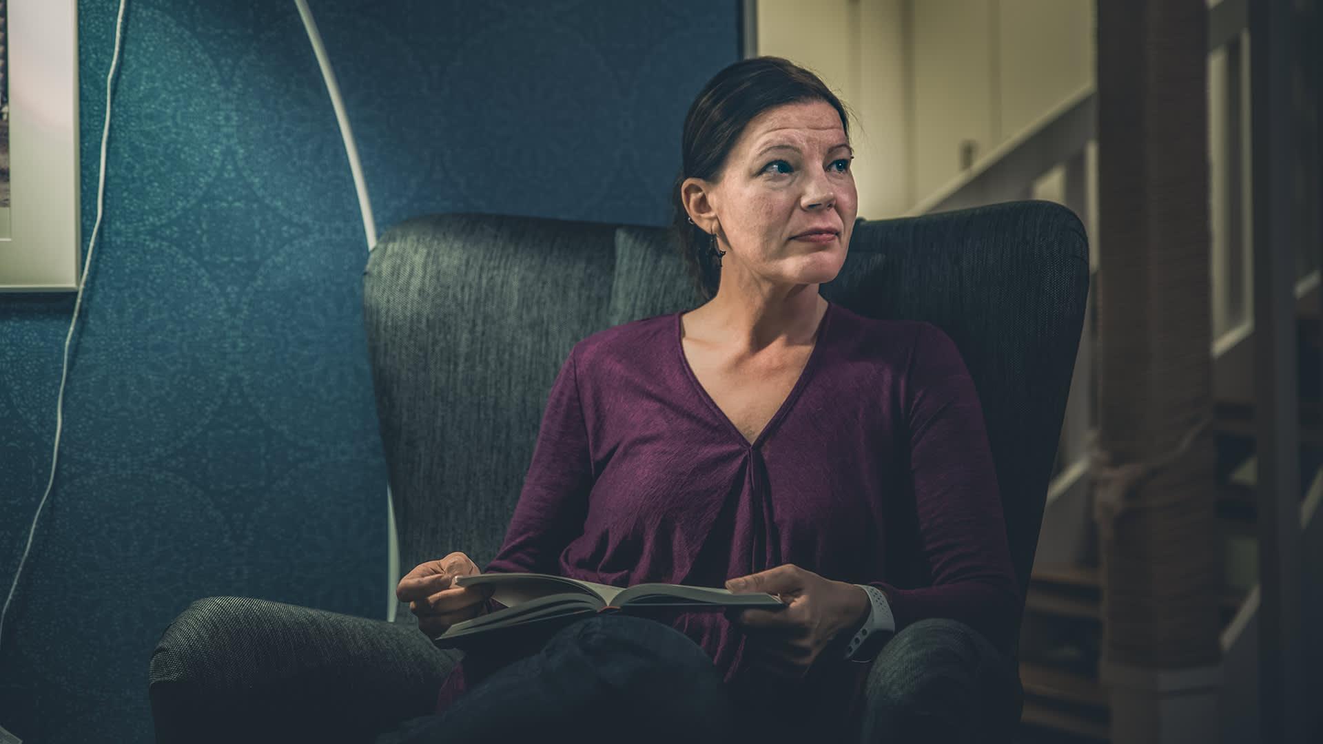Nainen istuu nojatuolissa