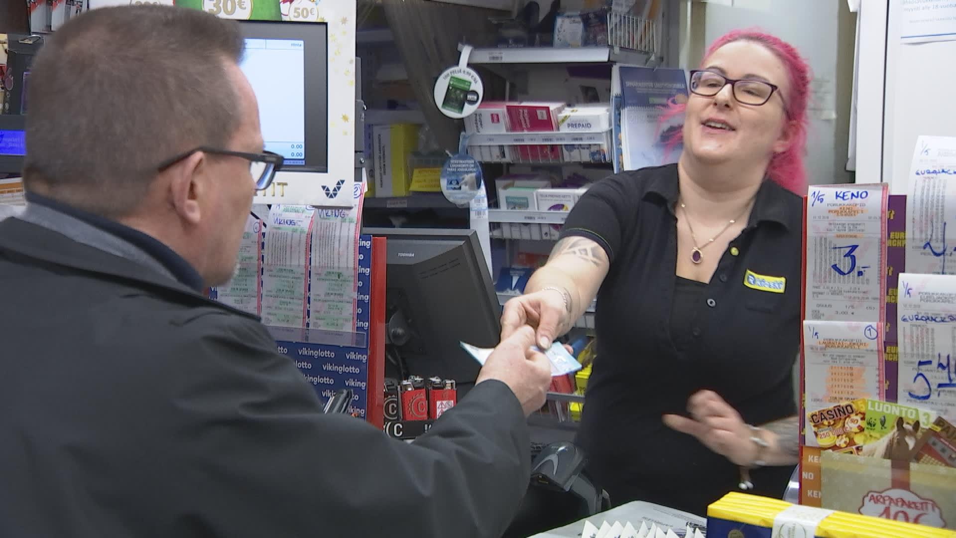 R-kioskin myyjä ojentaa toimittaja Matti Toivoselle 20 euron setelin, jonka Matti on nostanut tililtään oston yhteydessä.