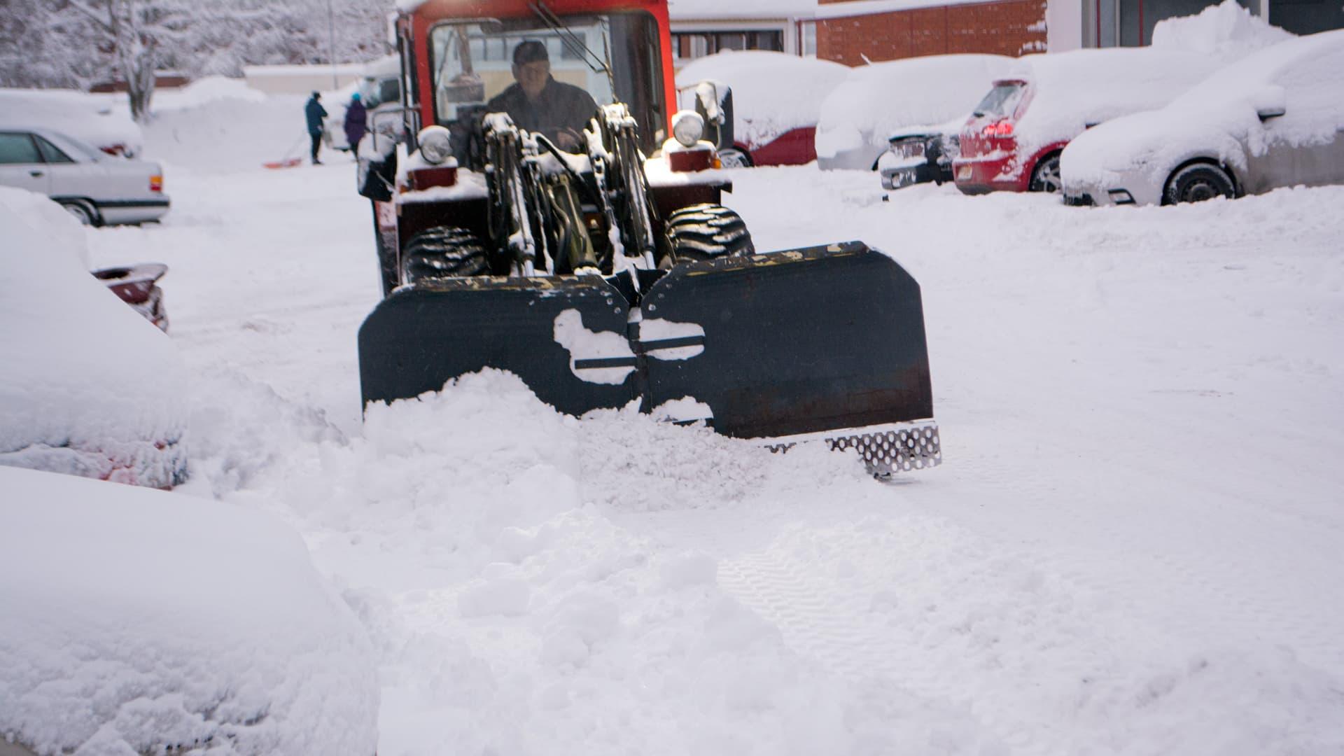Yrittäjä Teemu Räsänen auraa lunta Kuopion Männistössä.