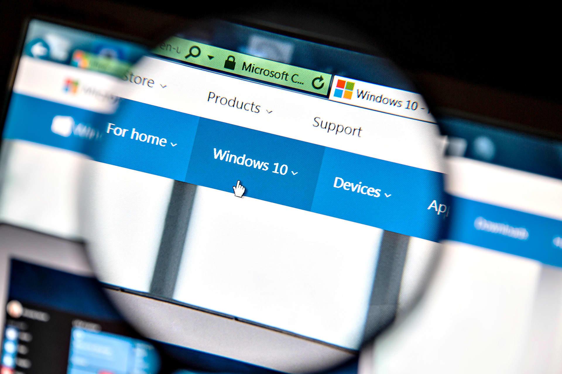 Suurennuslasin läpi näkyy tietokoneen näytöllä Windows 10:n alavalikko ja käsi-ikoni.