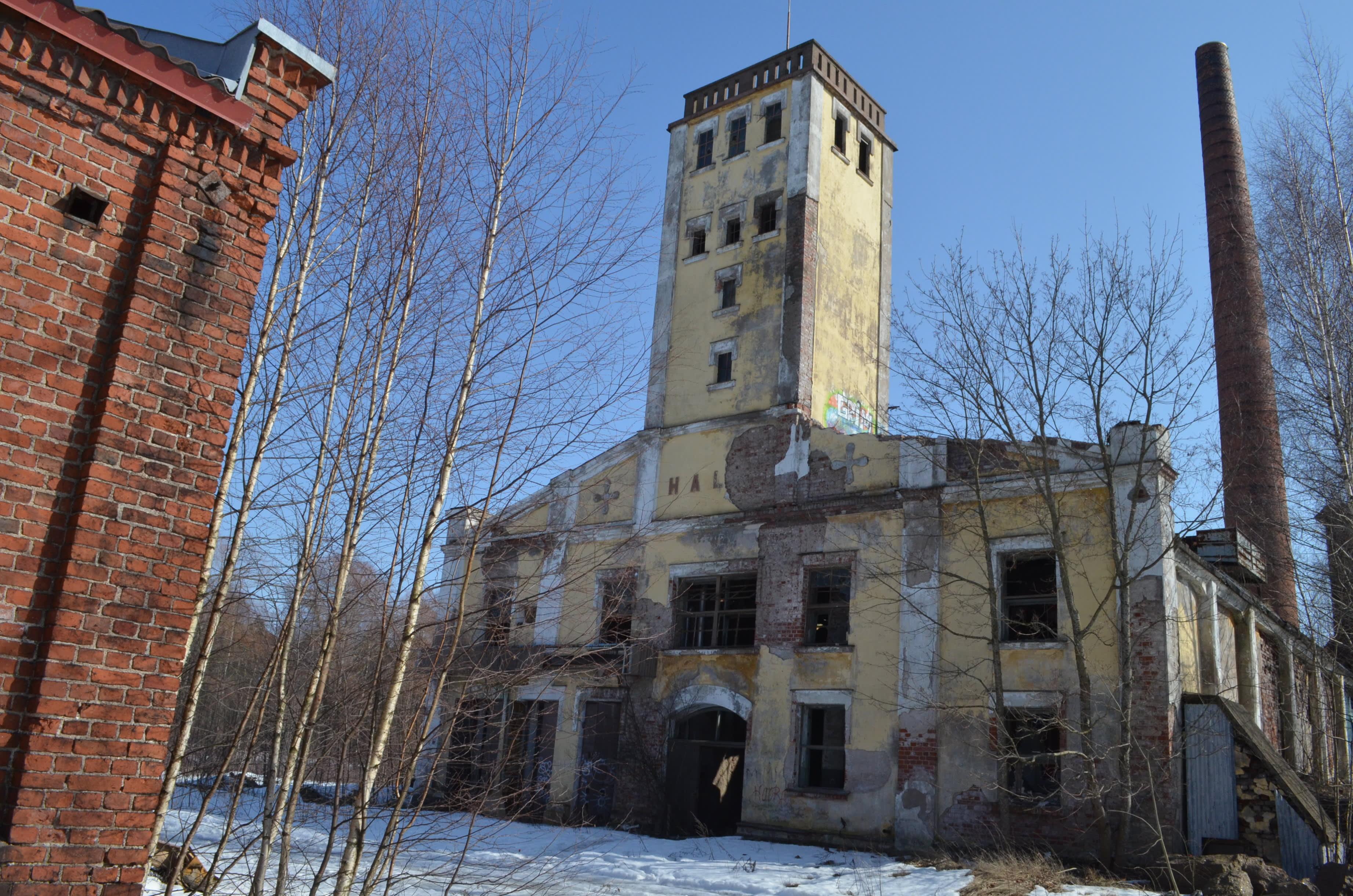 Vasemmassa reunassa tiiliestä rakennetut rakennuksen nurkka, sen vieressä kellertävä vanha Hallan voimalaitosrakennus, kuva keväältä 2016.