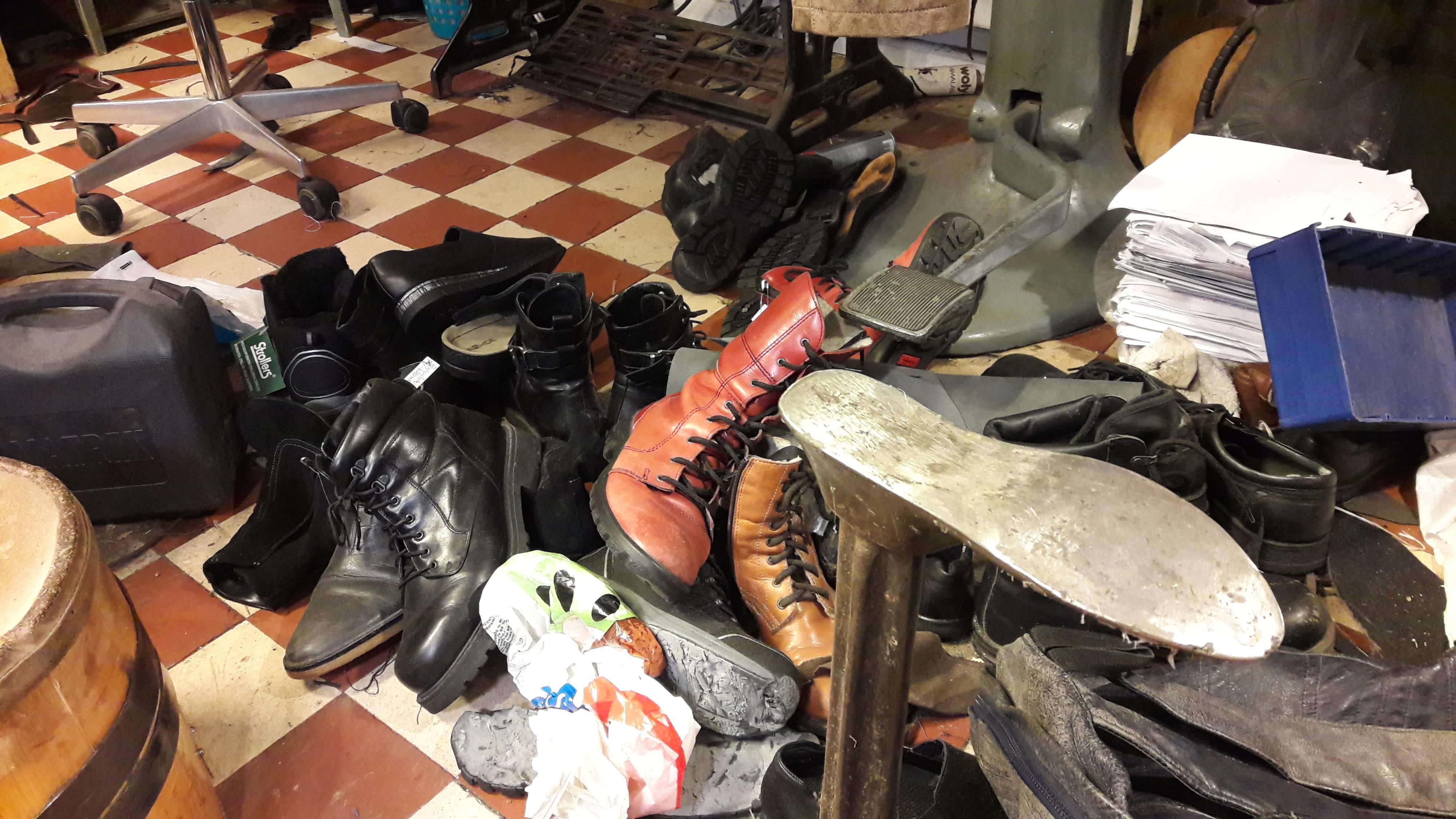 Erilaisia kenkiä kasassa odottamassa suutarin apua.