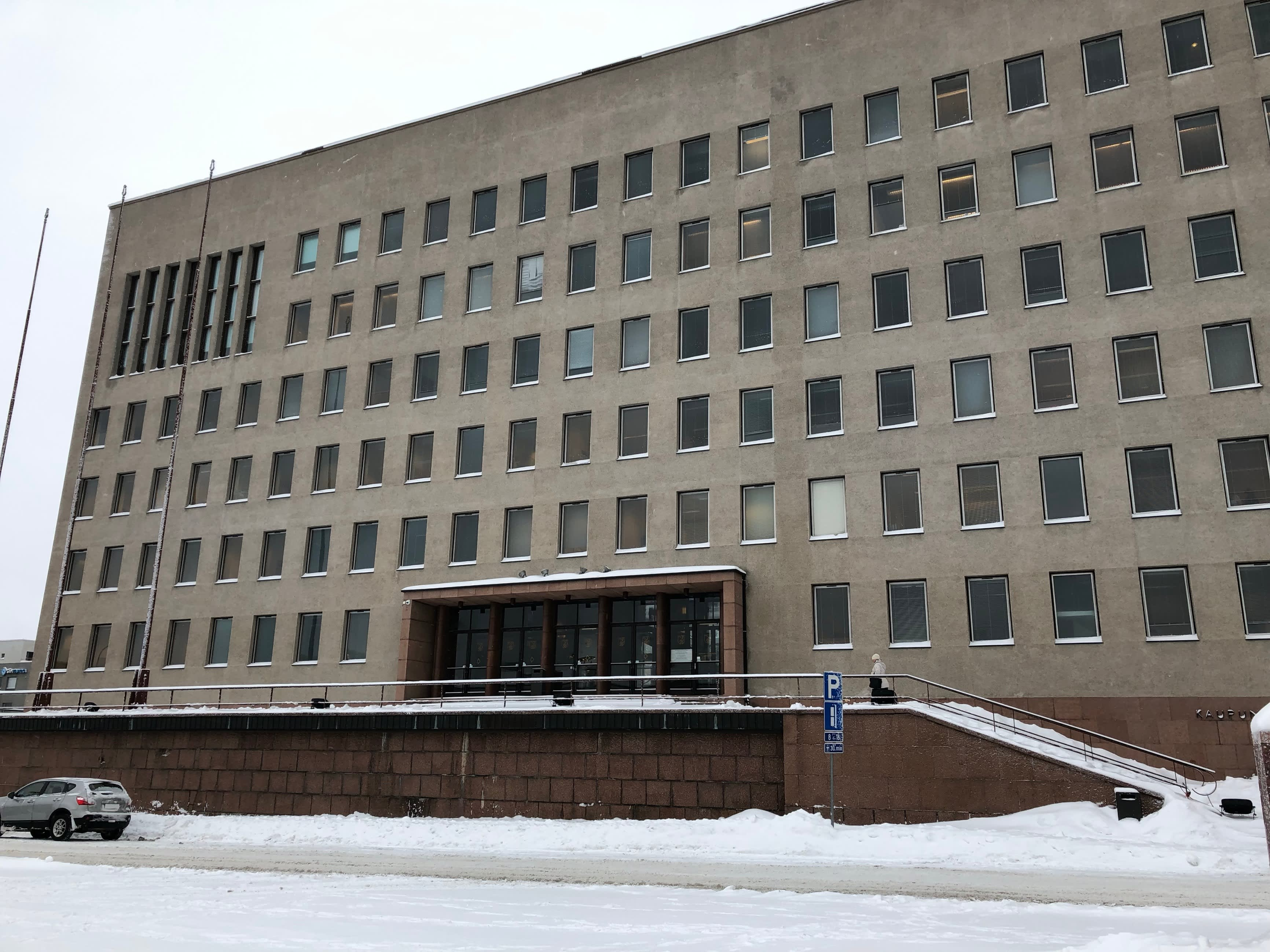 Kotkan kaupungintalon julkisivu kohoaa lumisesta maisemasta.