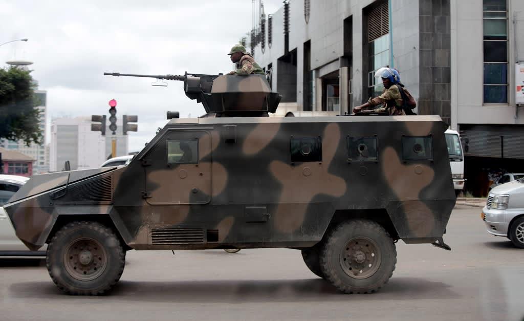 Maastokuvioitu panssariajoneuvo seisoo kadulla. Auton konekivääritornissa on mies lippalakki päässään. Auton takaosassa seisoo mellakkakypärään sonnustautunut mies.