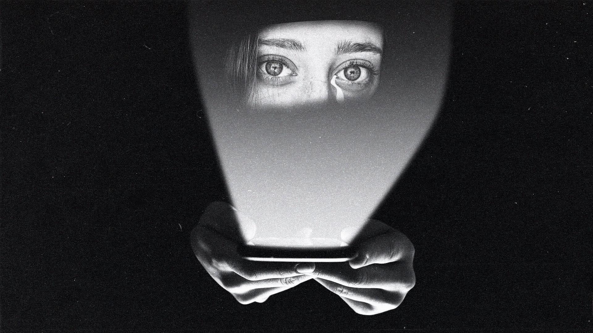 Kuvamanipulaatiossa naisen kasvot kännykän näytön heijastuksessa.